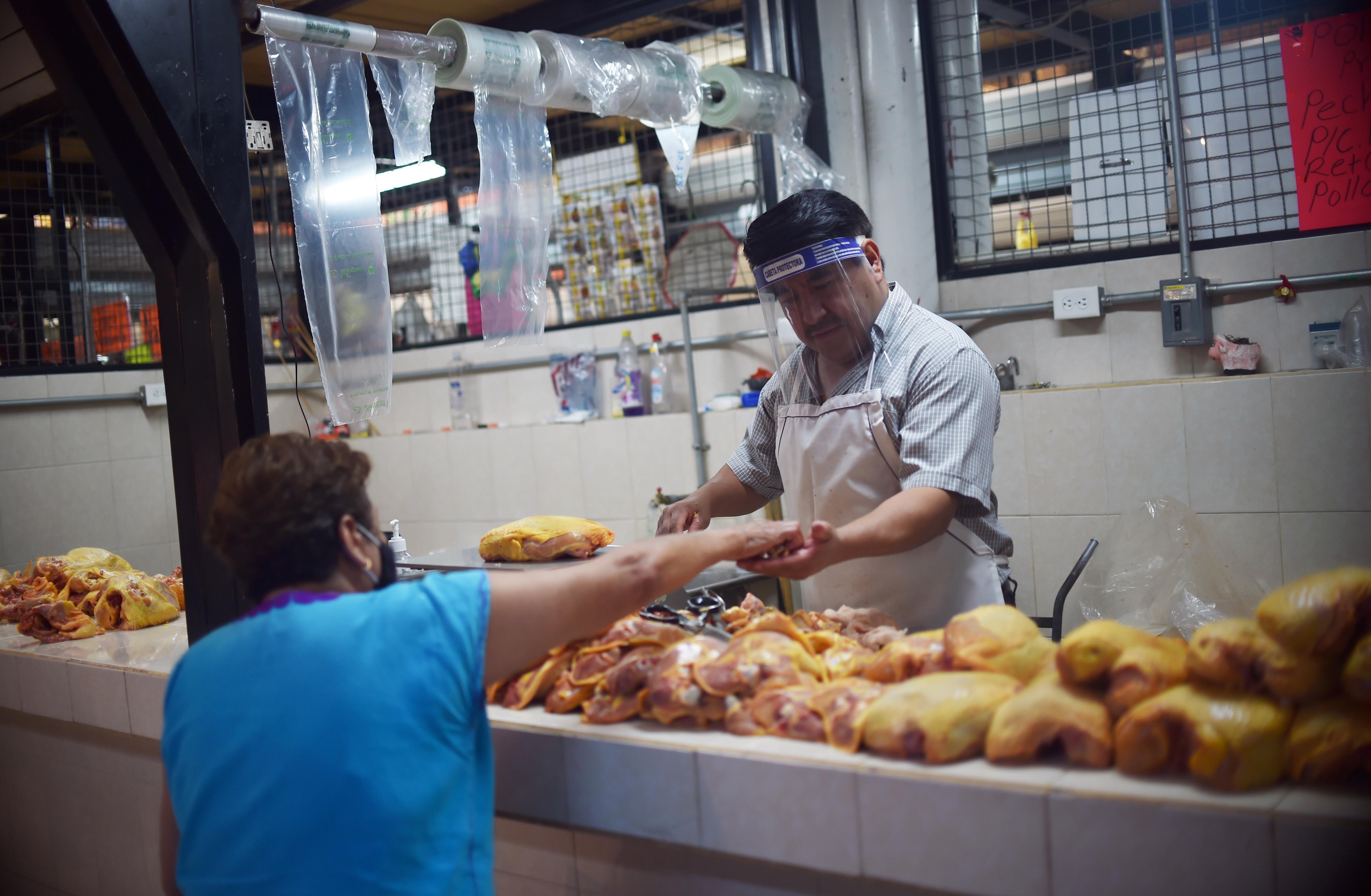Un vendedor de pollo atiende a un cliente en un mercado popular en la Ciudad de México el 29 de junio de 2020. (Foto: RODRIGO ARANGUA / AFP)