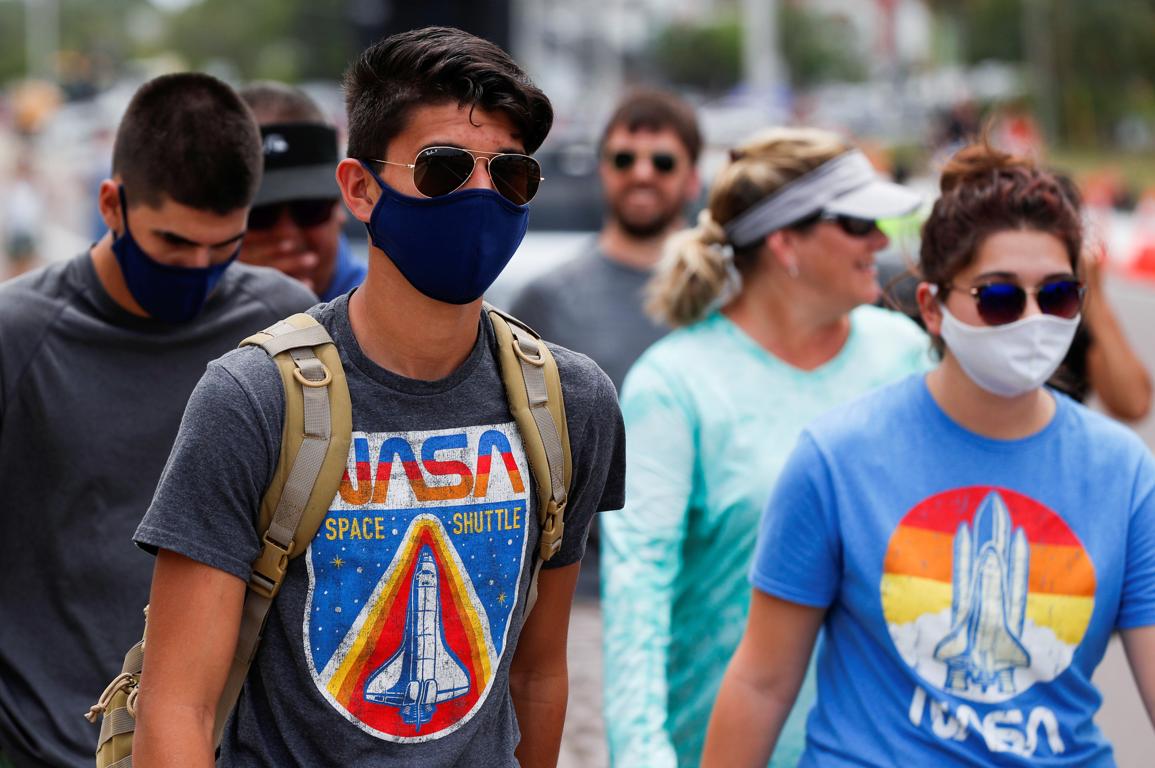 People wearing NASA'S T-shirts attend to watch the launching of a SpaceX Falcon 9 rocket and Crew Dragon spacecraft carrying NASA's astronauts Douglas Hurley and Robert Behnken during NASA's SpaceX Demo-2 mission to the International Space Station from NASA's Kennedy Space Center, in Cape Canaveral, Florida, U.S. May 30, 2020. REUTERS/Scott Audette