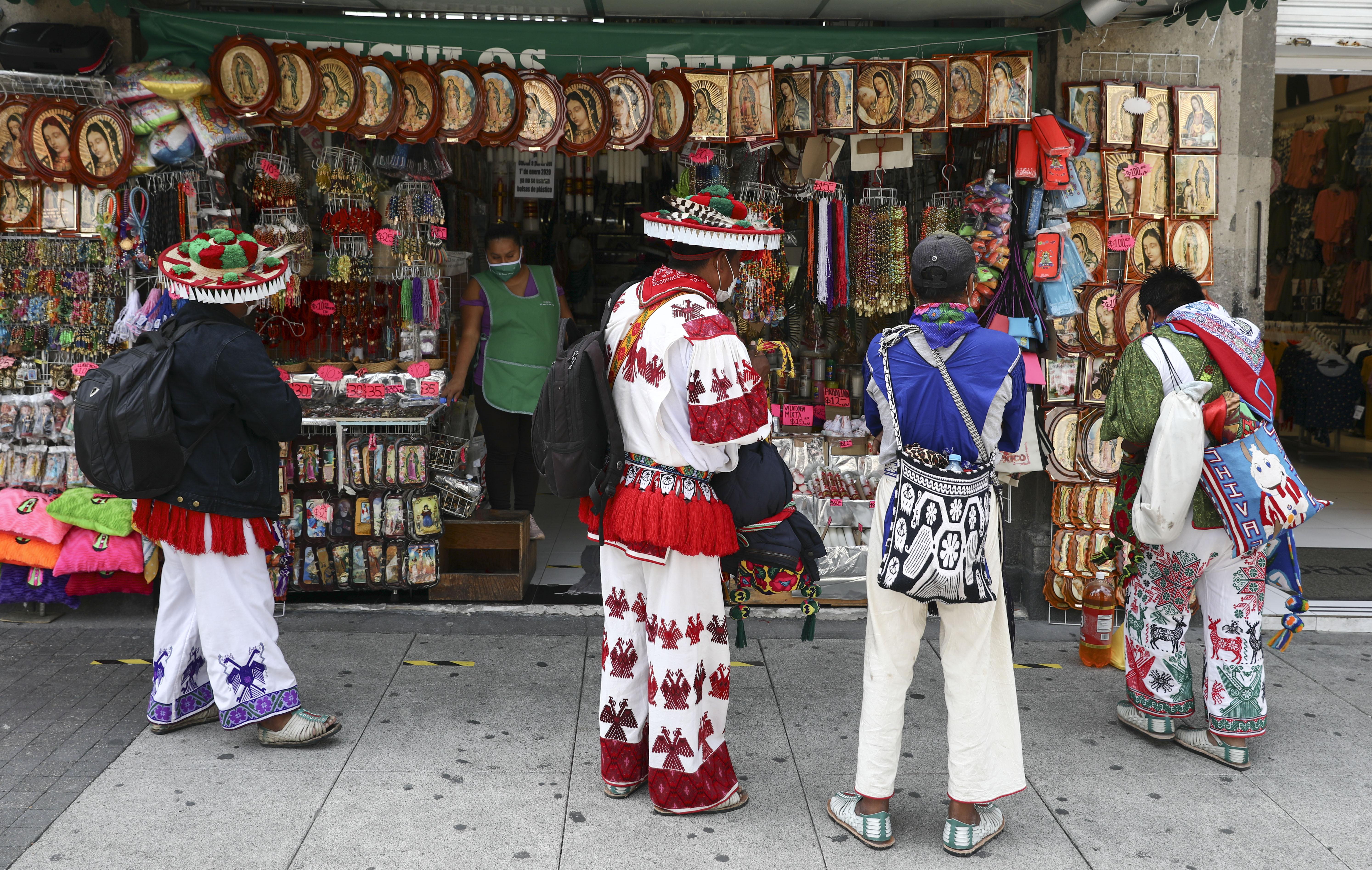 Los hombres indígenas huicholes observan imágenes religiosas a la venta fuera de la Basílica de Nuestra Señora de Guadalupe en la Ciudad de México, el lunes 29 de junio de 2020. (Foto: AP / Eduardo Verdugo)