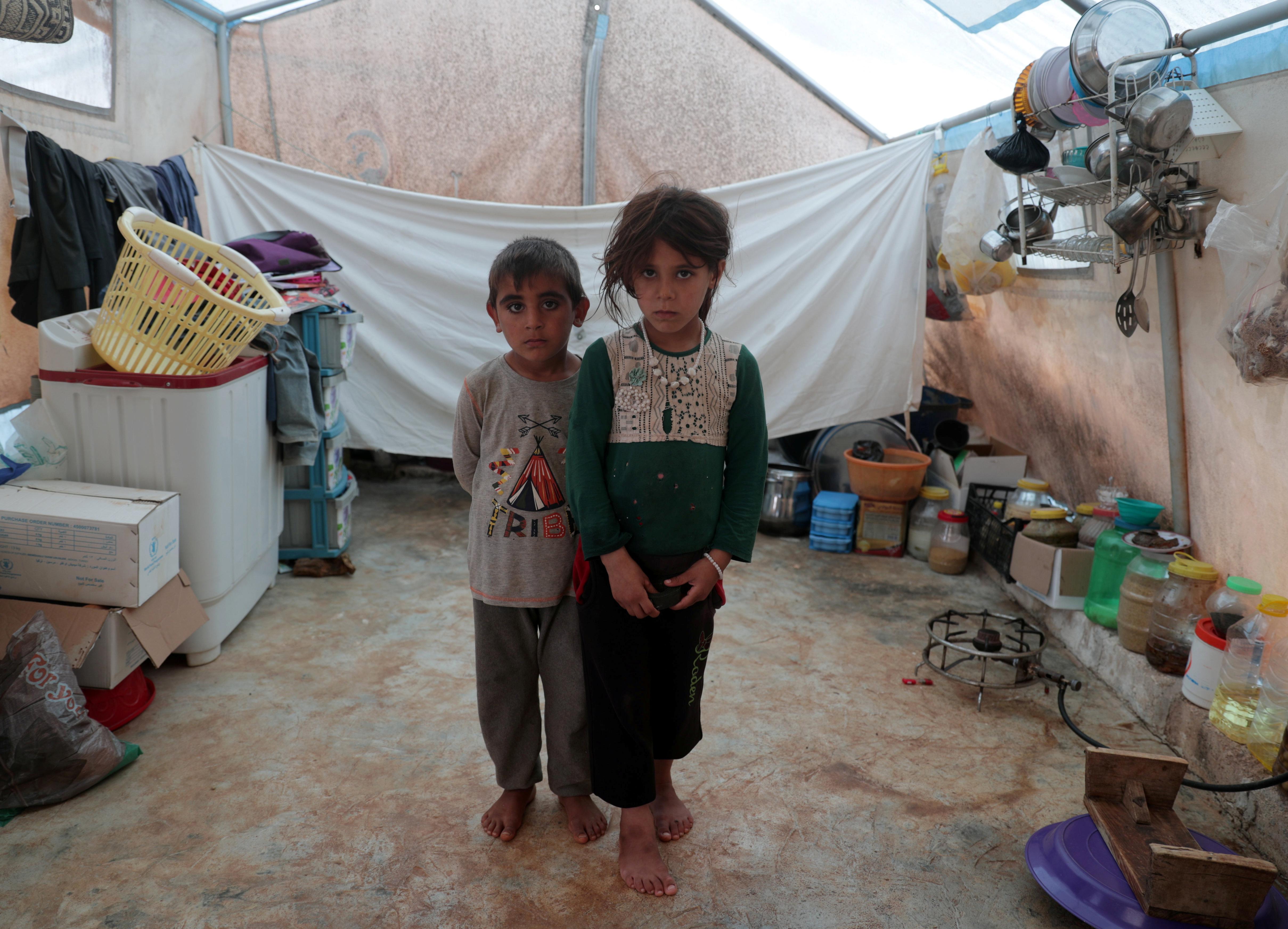 Jumana y Farhan al-Alyawi, gemelos sirios de 8 años desplazados del este de Idlib, posan para una foto en su tienda de campaña en el campamento de Atmeh (REUTERS / Khalil Ashawi)