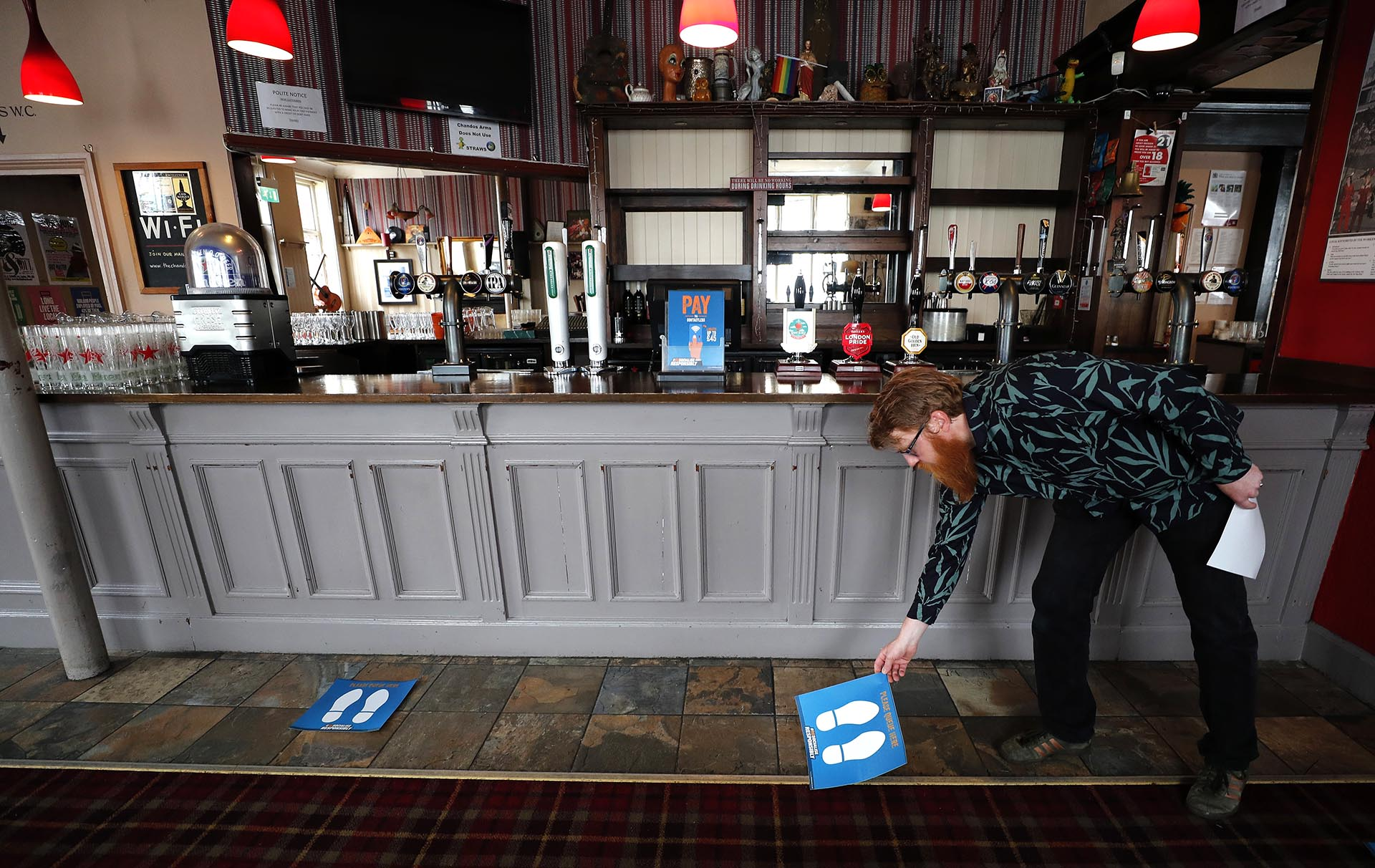 Un hombre acondiciona un pub para la reapertura (AP Photo/Frank Augstein)