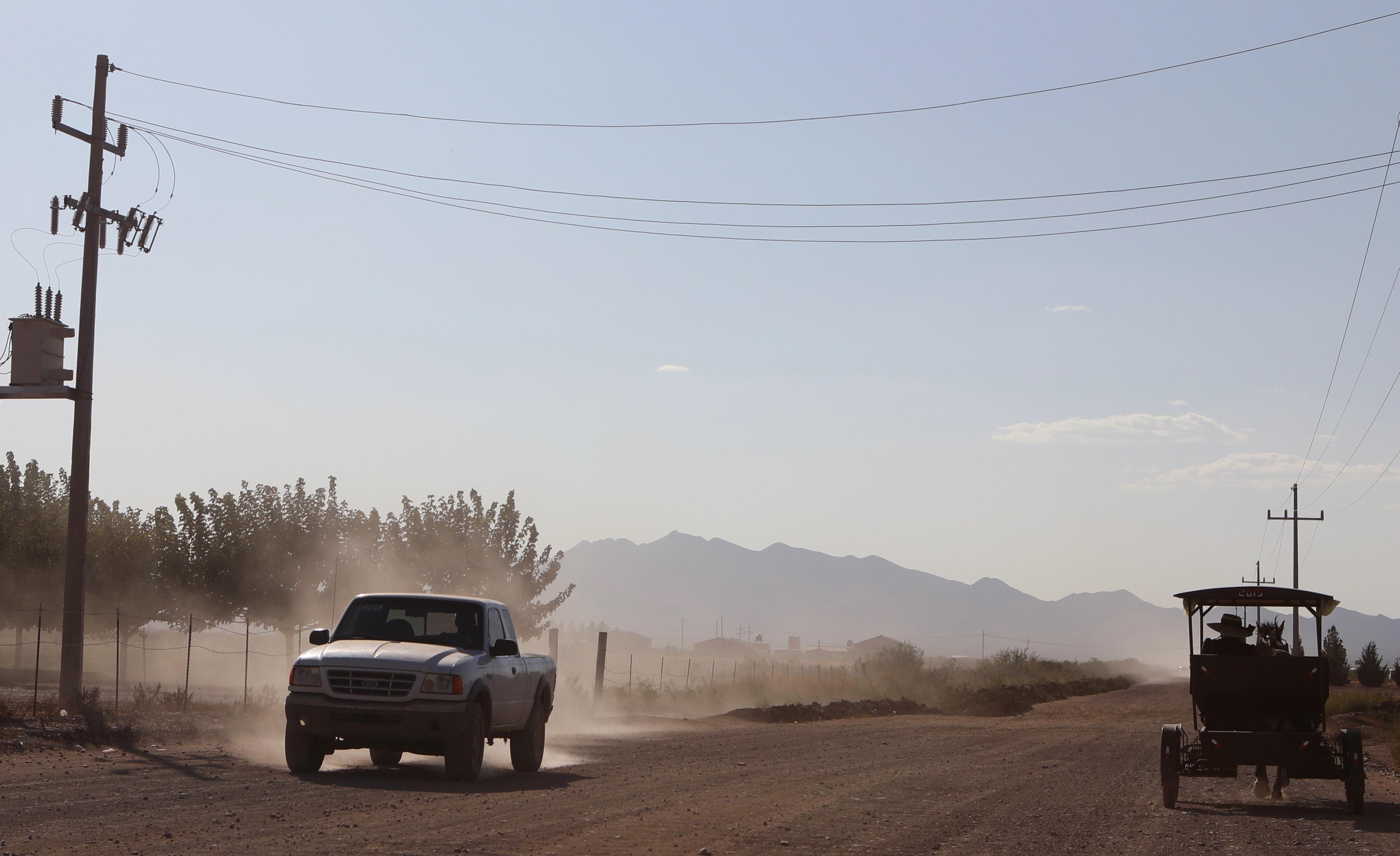 Un camión pasa cerca de una mujer menonita en un carro tirado por caballos en una comunidad menonita en el municipio de Ascensión, estado de Chihuahua, México, el 26 de septiembre de 2020.