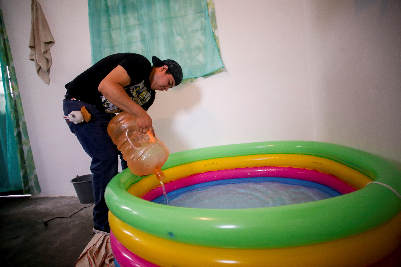 Miguel Flores Torres, de 24 años, llena de agua una piscina de parto inflable para su esposa embarazada Karla López Rangel, donde planea dar a luz en su casa, durante el brote del coronavirus (COVID-19), en Xochimilco, Ciudad de México, México. , 24 de mayo de 2020. Foto: REUTERS / Gustavo Graf