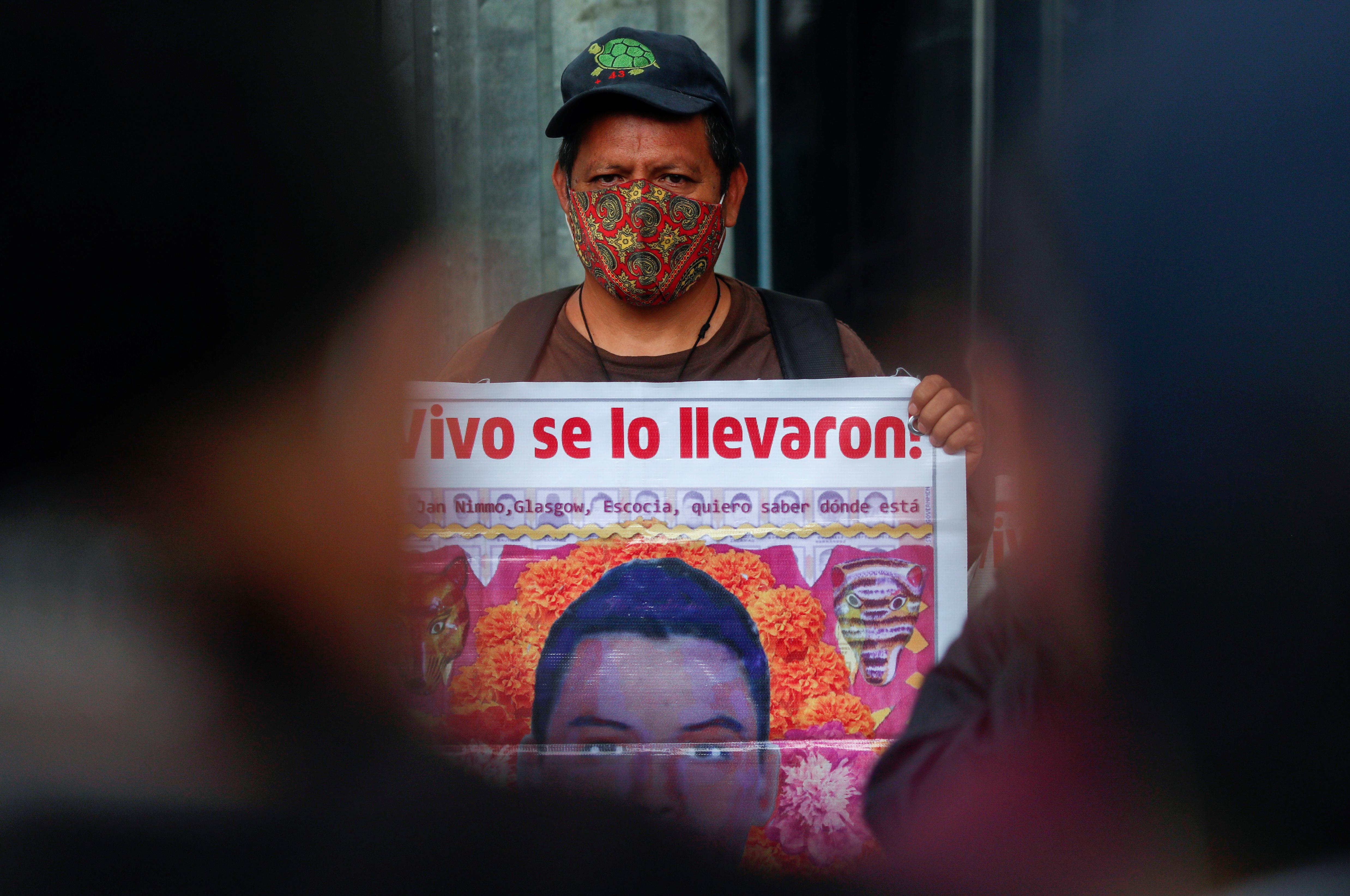 Un familiar de un estudiante desaparecido sostiene un cartel con su imagen mientras participa en una protesta frente a la Fiscalía General de la República, antes del sexto aniversario de la desaparición de 43 estudiantes de la Facultad de Formación de Maestros de Ayotzinapa, en la Ciudad de México, México 25 de septiembre, 2020.