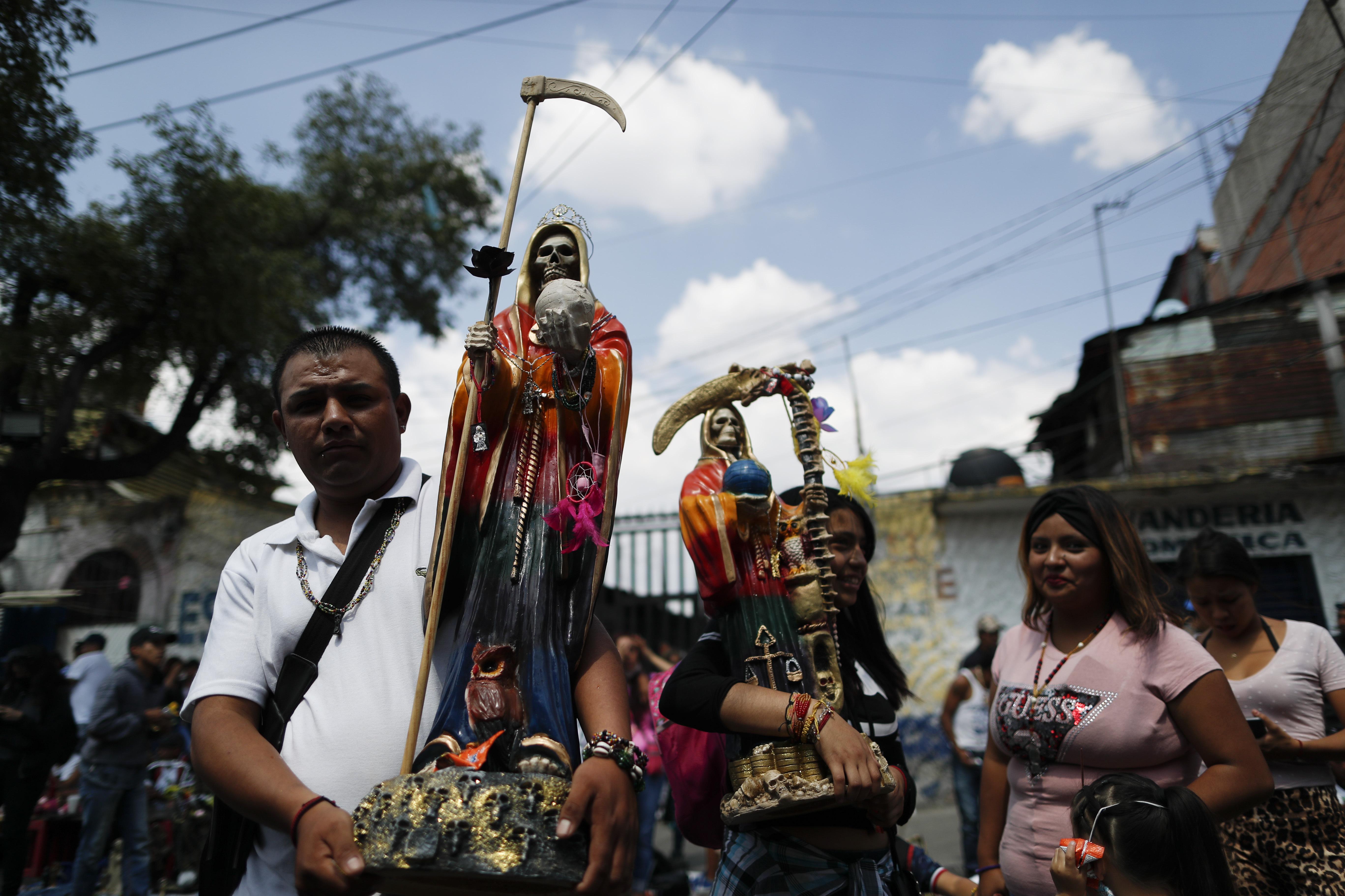 Los devotos llevan estatuas de la Santa Muerte mientras esperan en la fila para presentar sus respetos en su altar en el barrio de Tepito, Ciudad de México, el lunes 1 de junio de 2020. (Foto: AP / Rebecca Blackwell)
