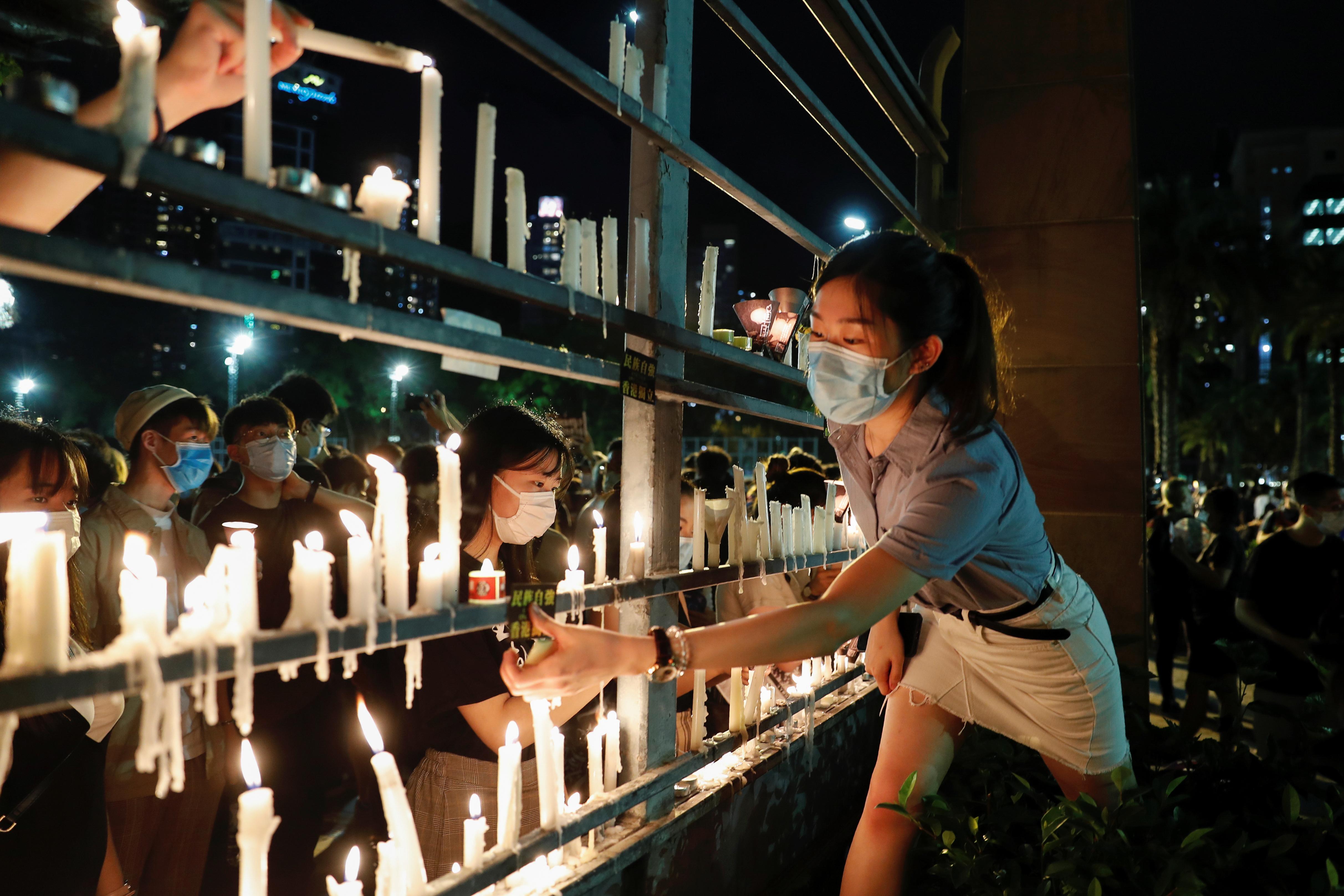 Una joven deja su vela junto a otras (REUTERS/Tyrone Siu)