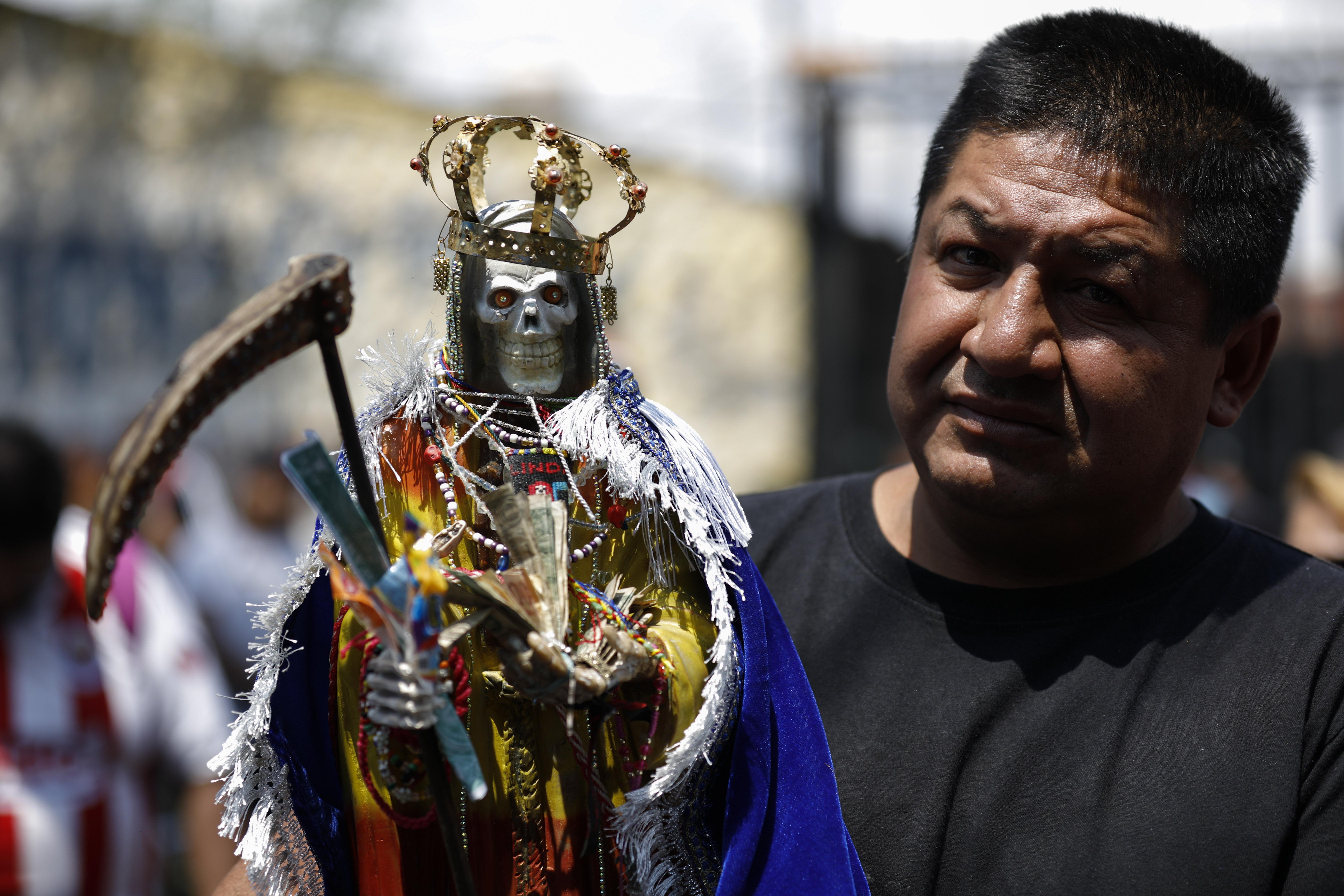 Un hombre lleva una estatua de la Santa Muerte. (Foto: AP / Rebecca Blackwell)