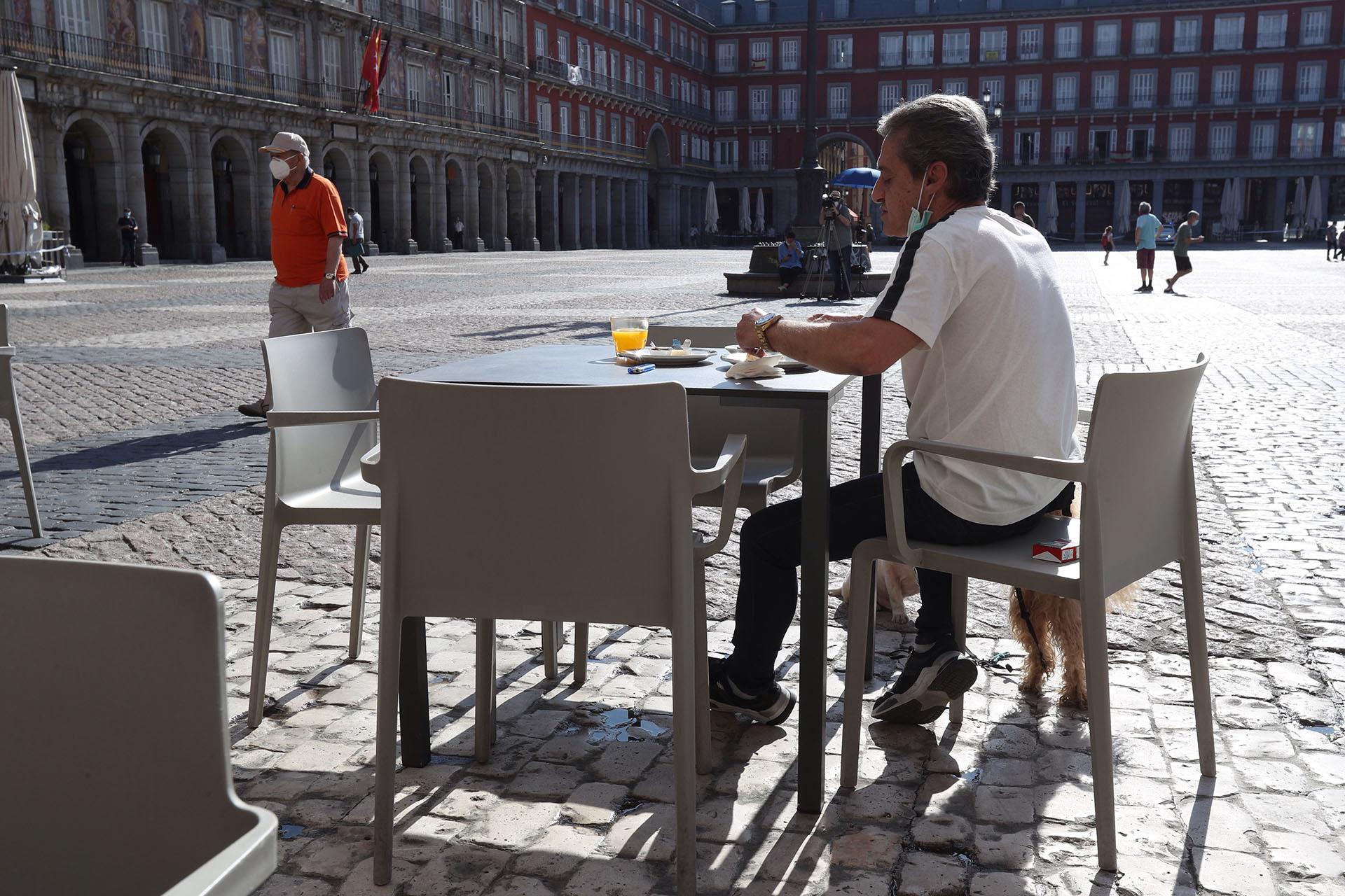 Un hombre desayuna en la terraza de un bar de la Plaza Mayor en Madrid este lunes, primera jornada de la fase 1 en la que la reapertura de las terrazas de los bares a un 50 % de su aforo y el acceso a los grandes parques son dos las principales novedades de esta nueva etapa. (EFE/Kiko Huesca)