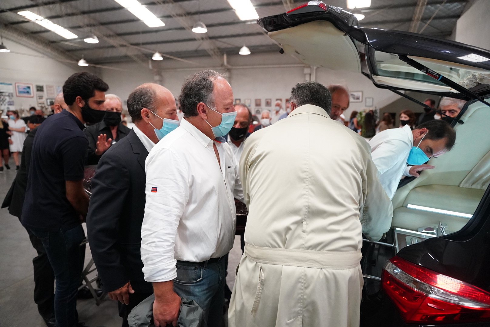 Sus familiares y amigos terminan de poner el féretro en el coche fúnebre.
