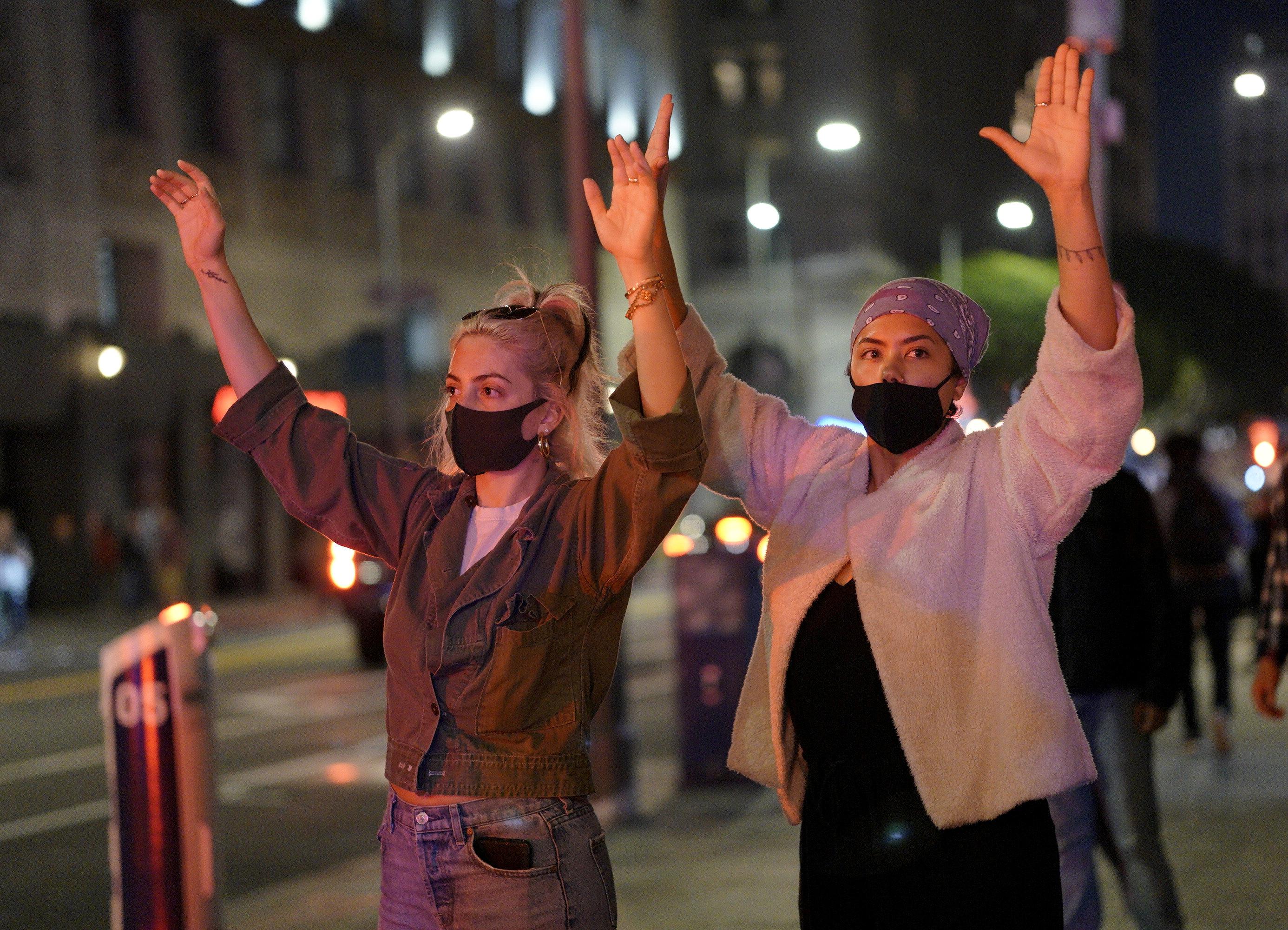 Mujeres con las manos en alto frente a la policía en Los Angeles