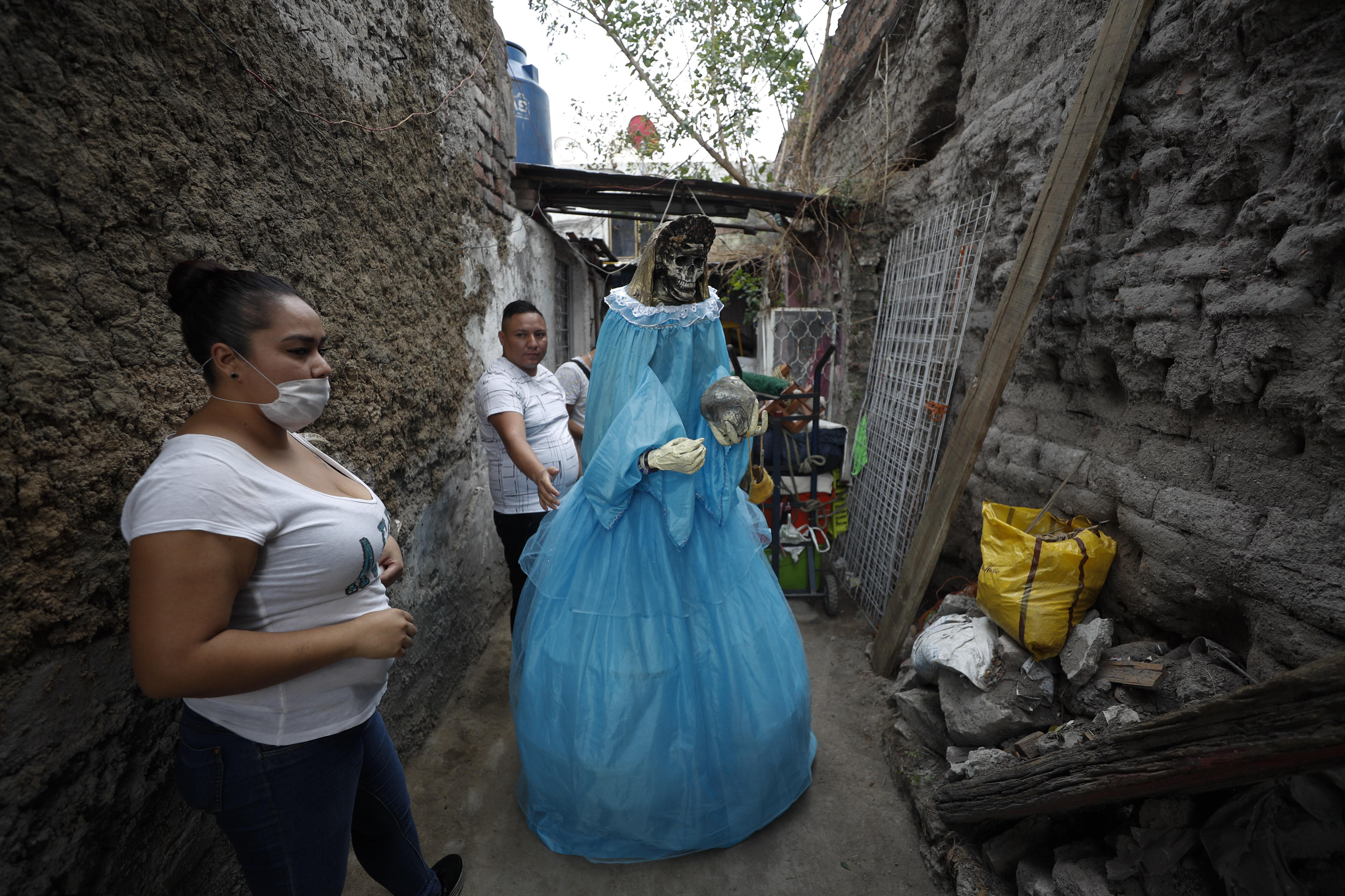 Los vecinos ayudan a devolver una figura gigante de la Santa Muerte a una casa después de que se exhibiera en la calle para celebrar el día del festival mensual del santo. (Foto: AP / Rebecca Blackwell)