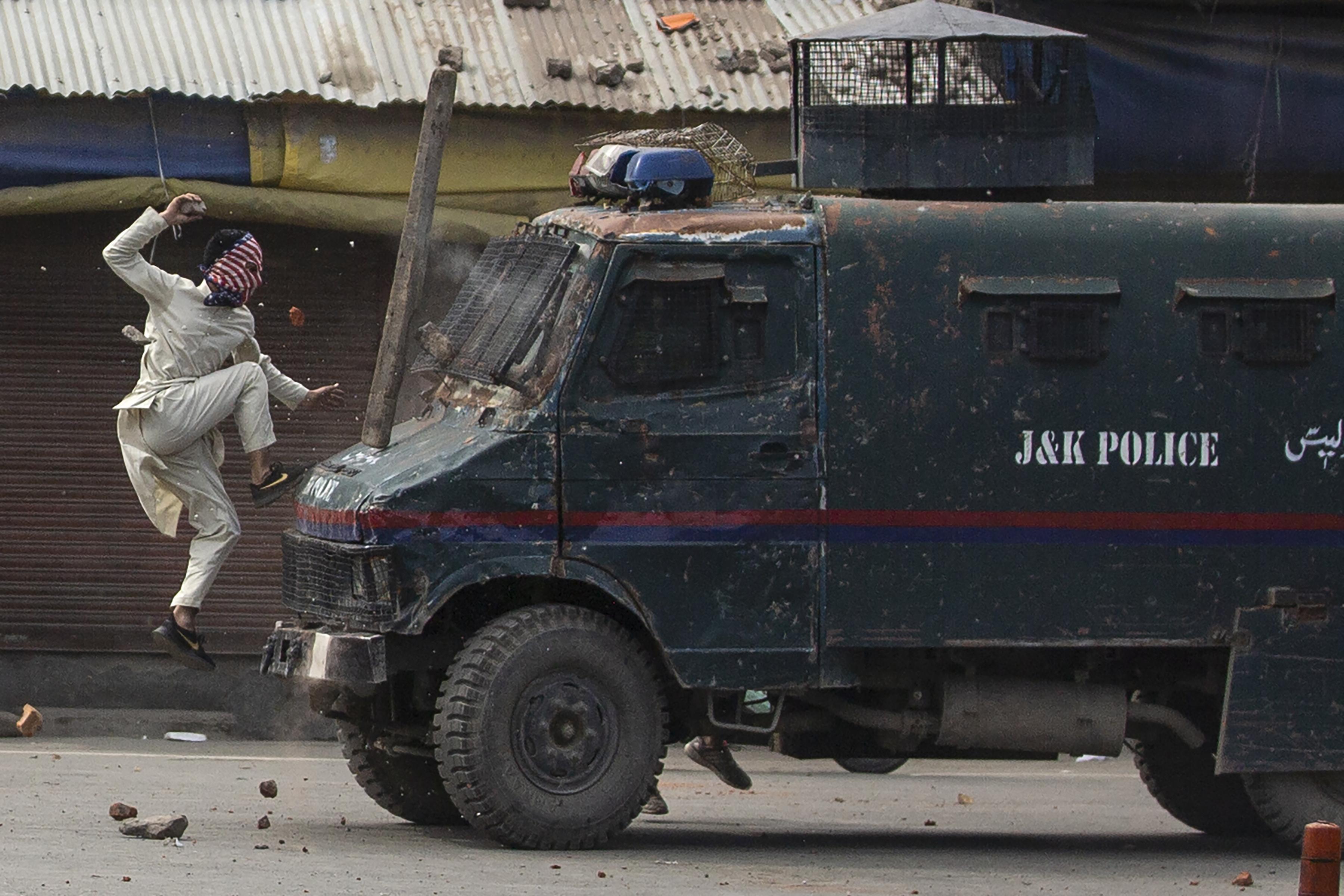Un manifestante enmascarado de Cachemira salta sobre el capó de un vehículo blindado de la policía india mientras le arroja piedras durante una protesta en Srinagar. (Foto AP / Dar Yasin)