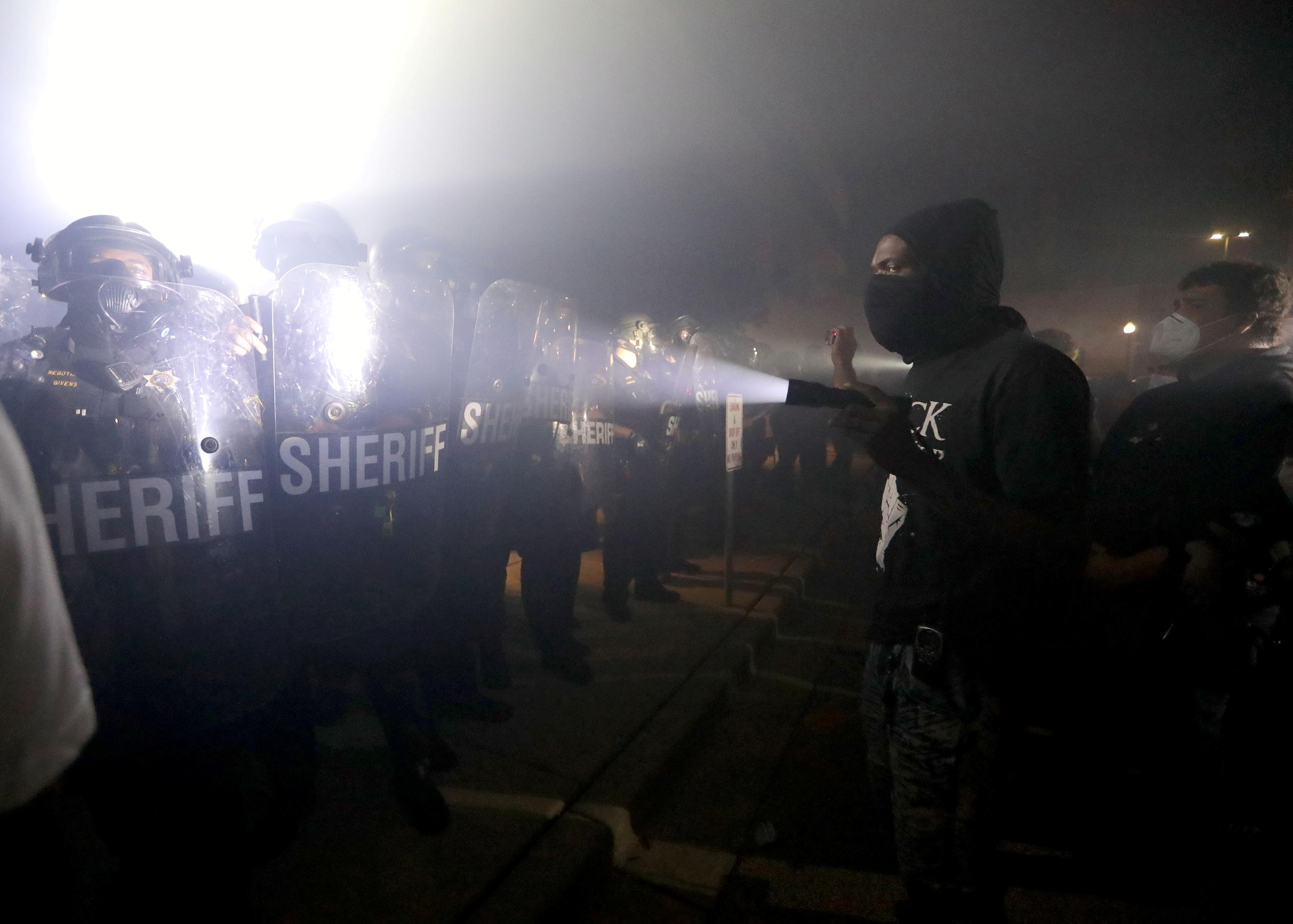 Un manifestante enciende una linterna en dirección a los agentes fuera del Departamento de Policía de Kenosha (Mike De Sisti / Milwaukee Journal Sentinel vía USA TODAY vía REUTERS)