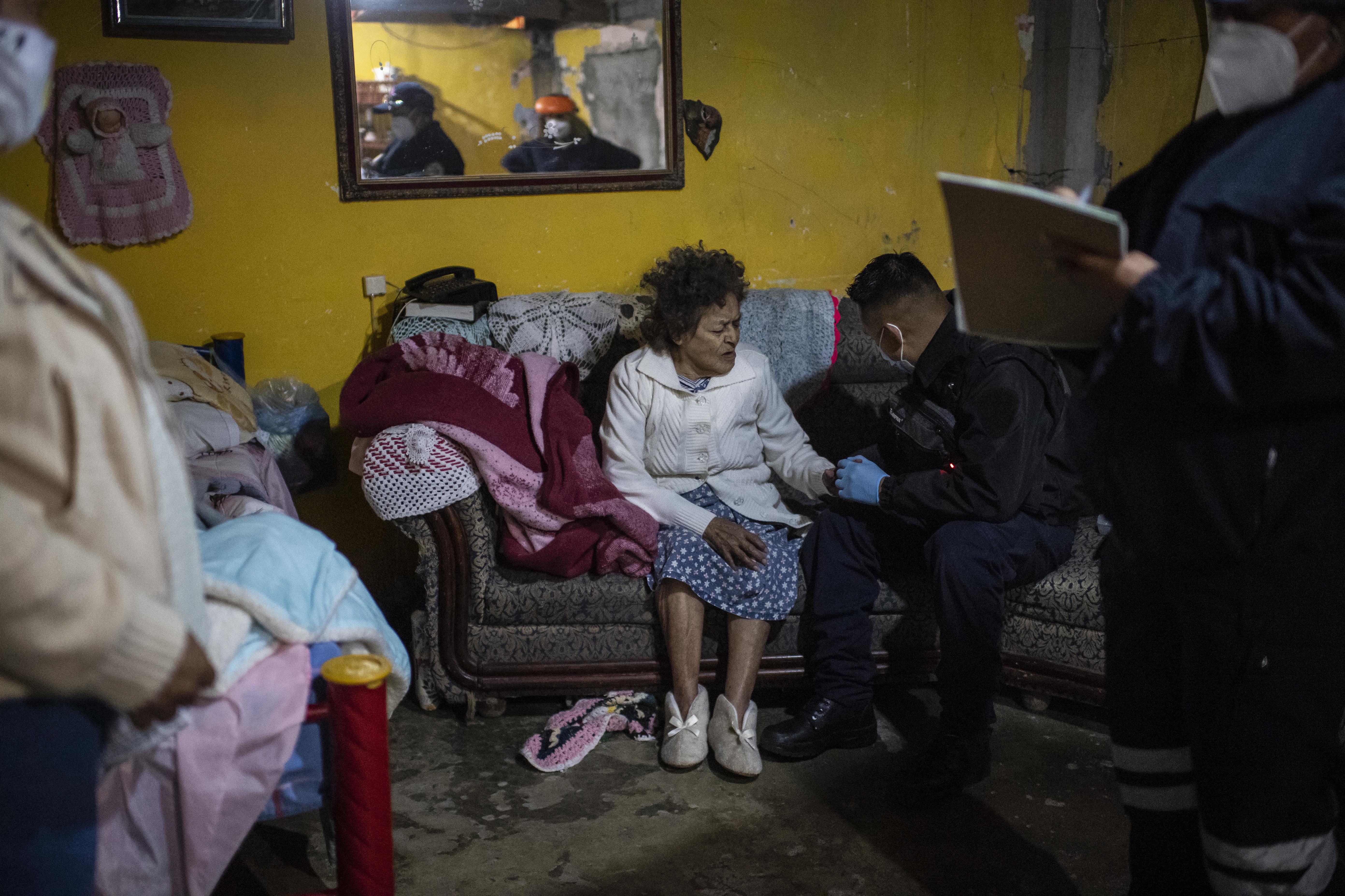 El paramédico Jesús Sholndick, de 29 años, revisa a una mujer hipoglucémica en Ciudad Nezahualcóyotl, Estado de México, México, el 18 de junio de 2020 durante la nueva pandemia de coronavirus de COVID-19. (Foto por Pedro PARDO / AFP)