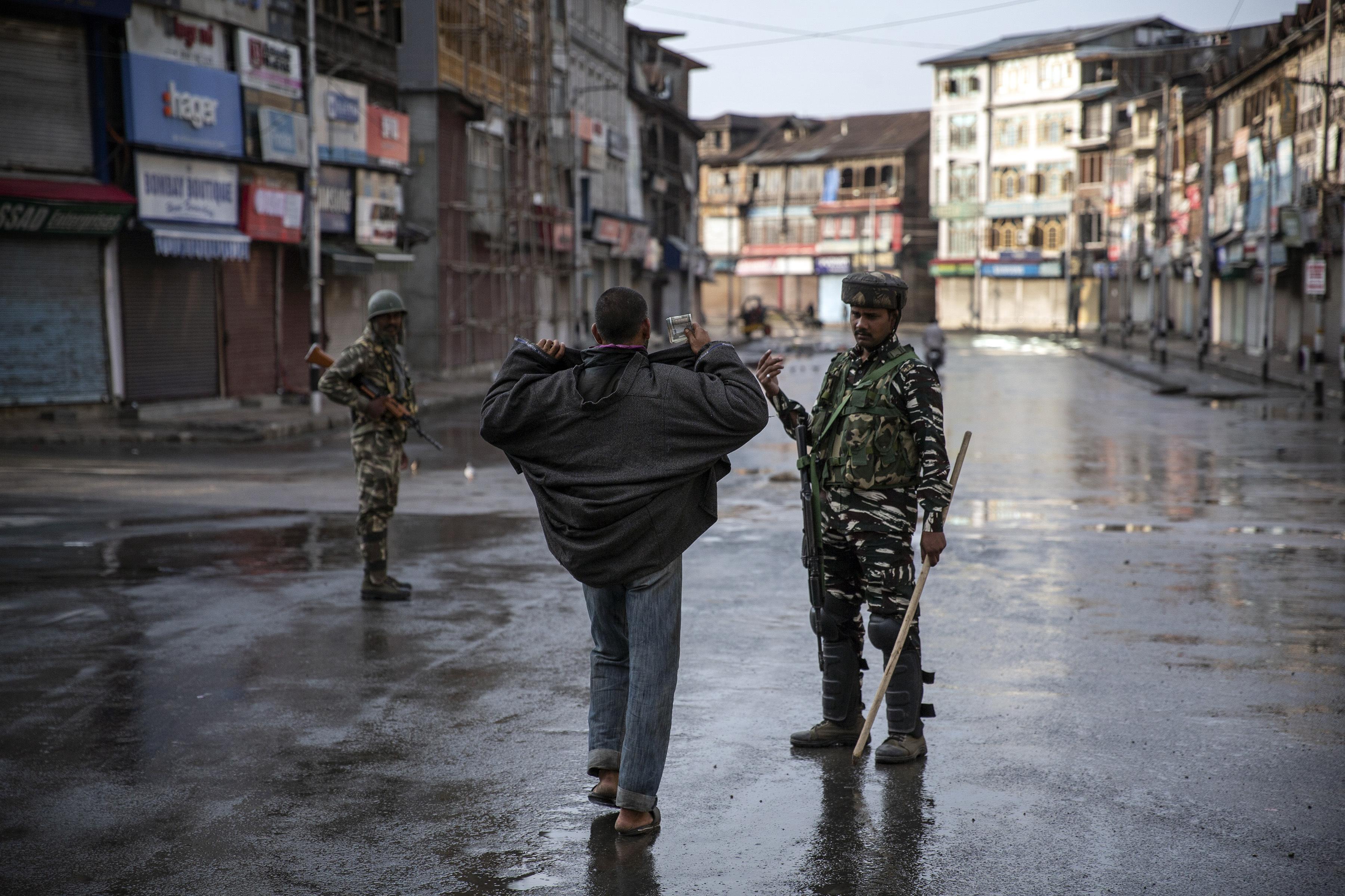 Un soldado paramilitar indio le ordena a un cachemir abrir su chaqueta antes de registrarlo durante el toque de queda en Srinagar, Cachemira controlada por los indios, el 8 de agosto de 2019. El hermoso valle del Himalaya está inundado de soldados y barricadas de alambre de púas. (Foto AP / Dar Yasin)