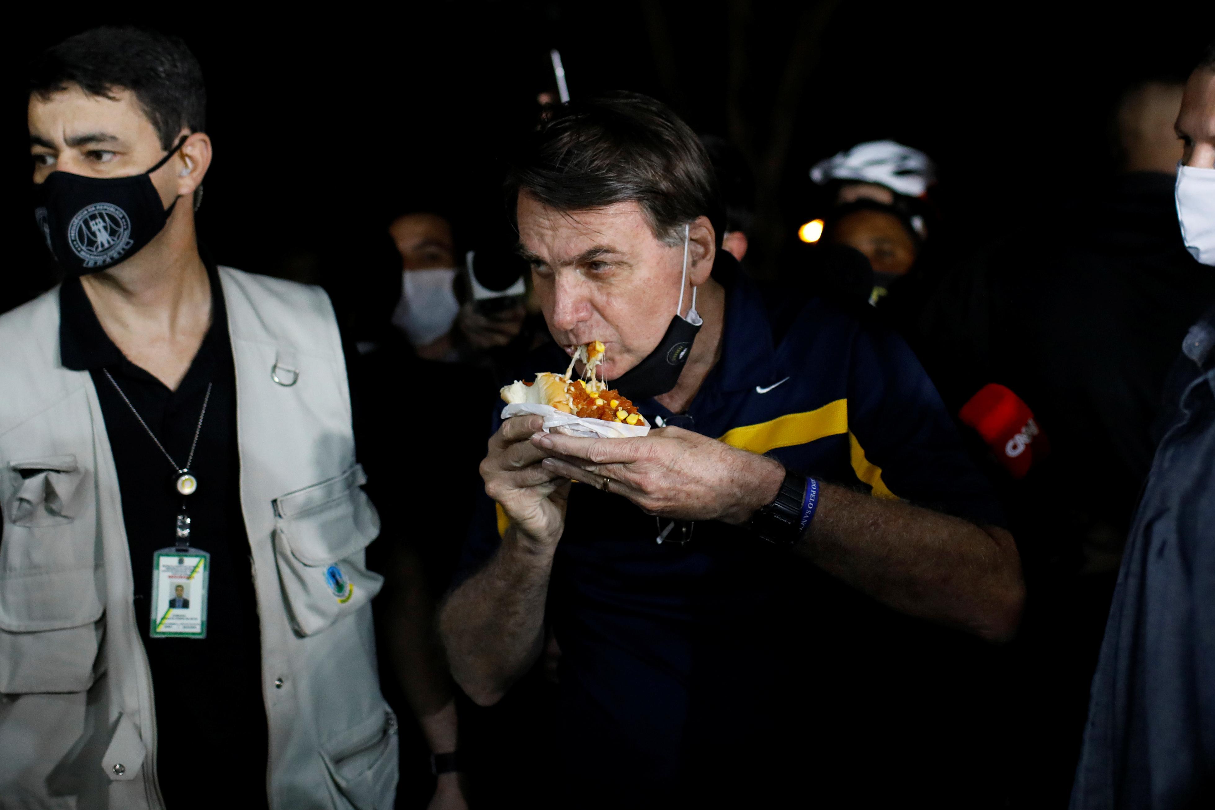 Bolsonaro comiendo un hotdog en una cafeteria en la calle, el 23 de mayo pasado REUTERS/Adriano Machado