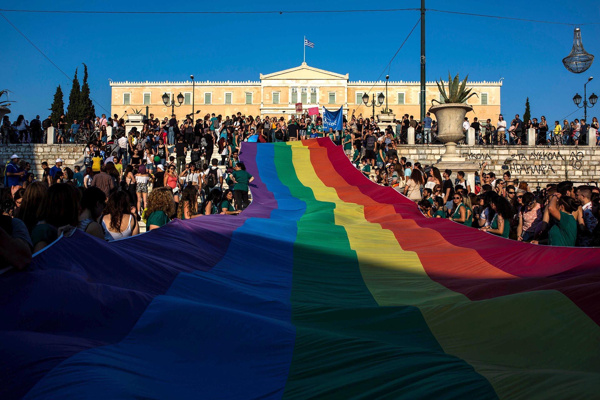 Una multitud sostiene una bandera gigante de arco iris frente al Parlamento griego en el sexto desfile del Orgullo en Atenas el 10 de junio de 2017