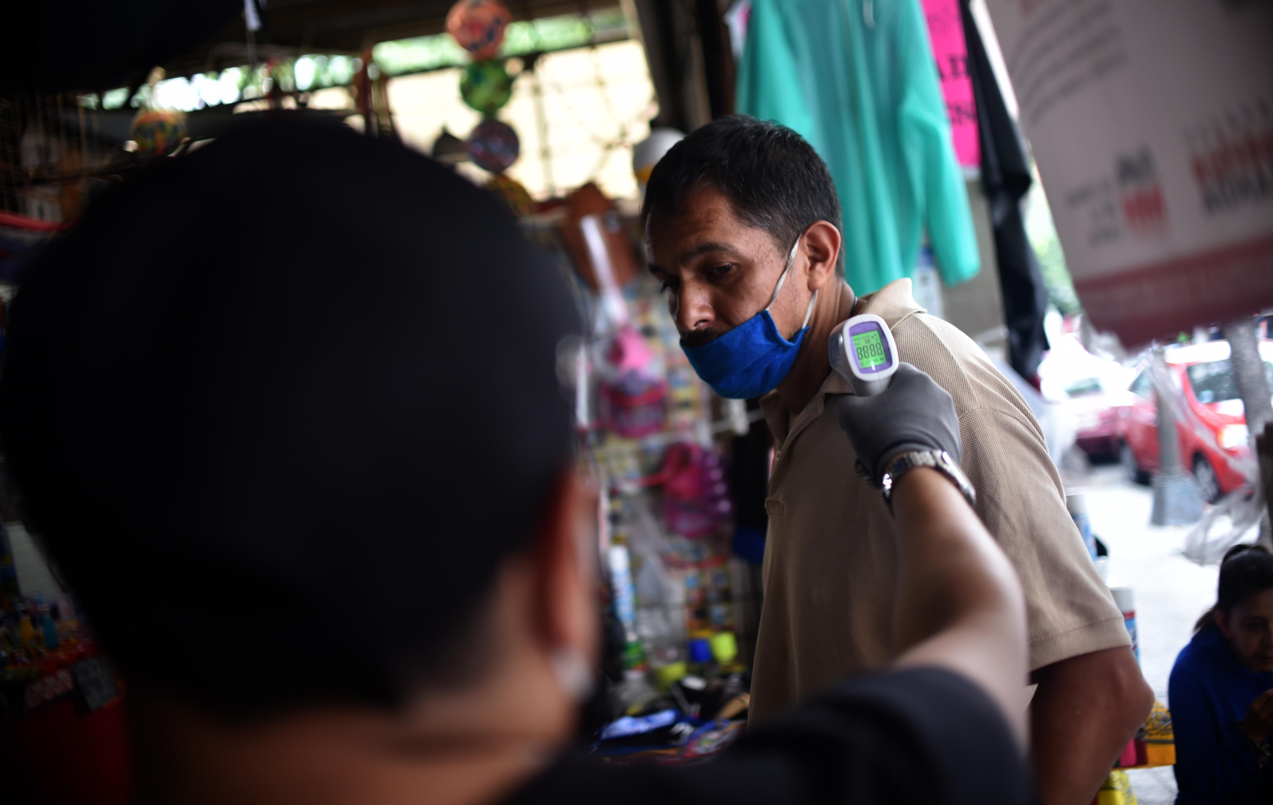 Un trabajador verifica la temperatura corporal de un cliente a la entrada de un mercado popular en la Ciudad de México el 29 de junio de 2020. (Foto: RODRIGO ARANGUA / AFP)