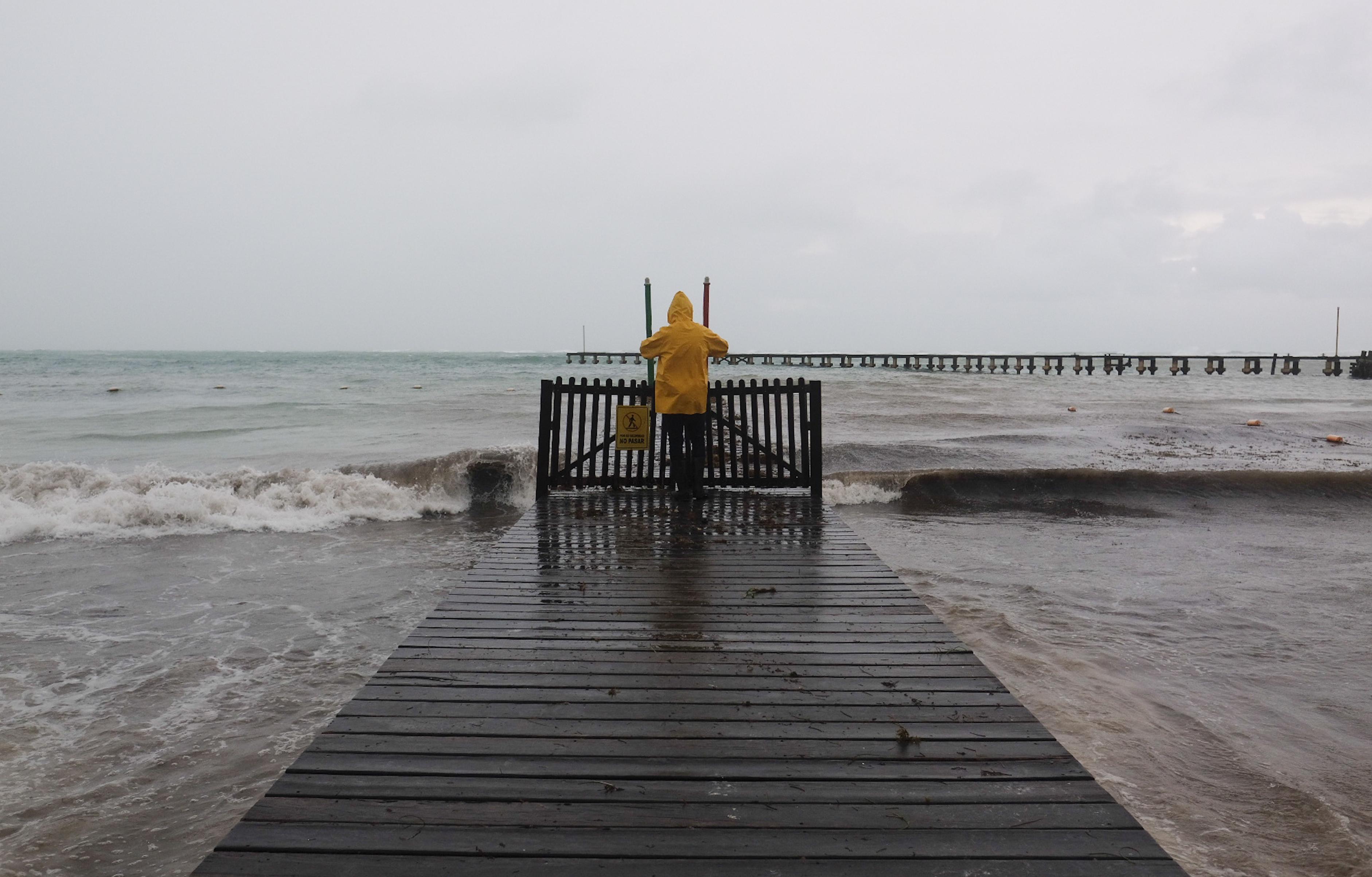 Un hombre toma fotografías del mar durante el paso del huracán Delta en Cancún, México, el miércoles 7 de octubre de 2020.