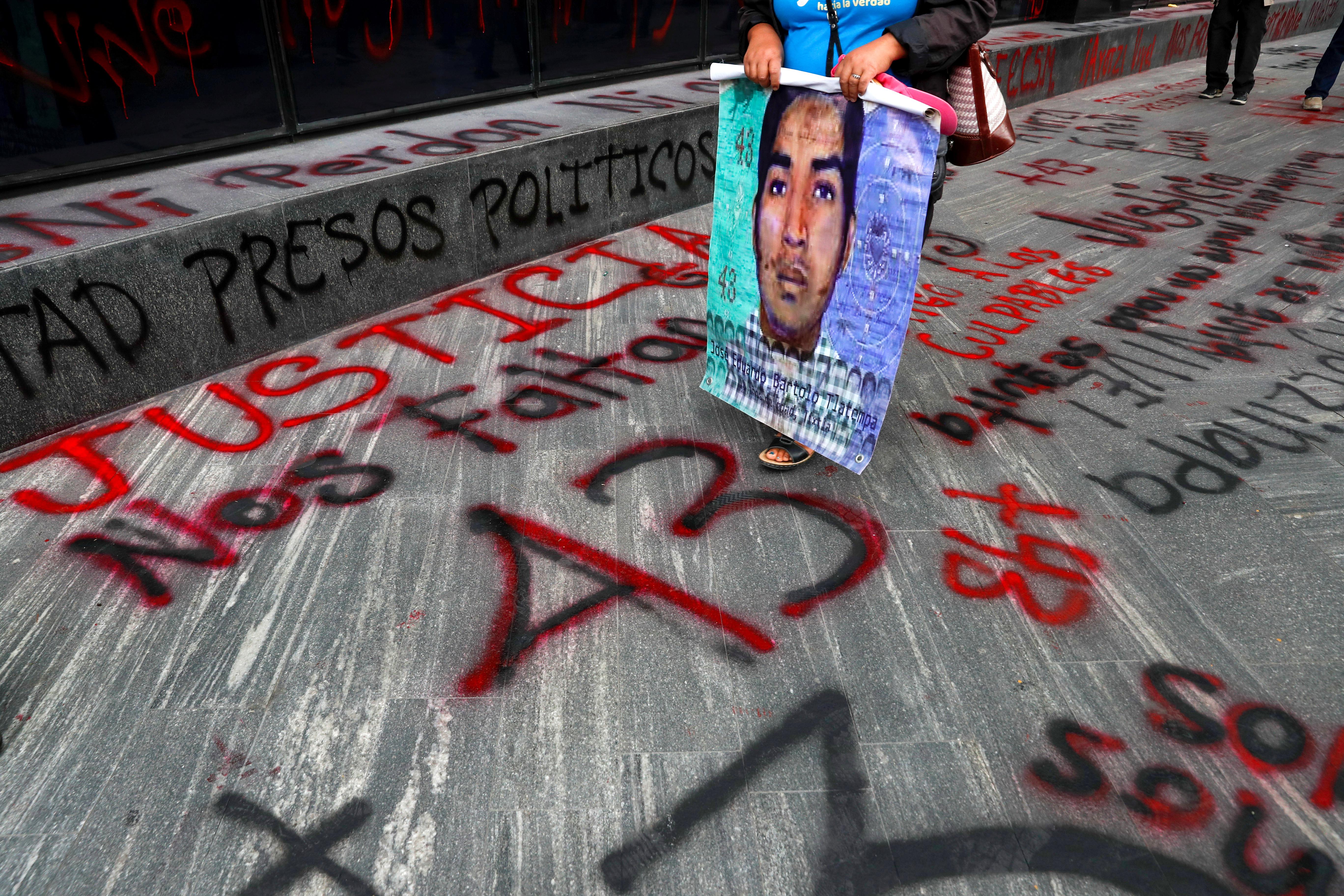 Un familiar de un estudiante desaparecido sostiene un cartel con su imagen mientras pasa junto a un cartel