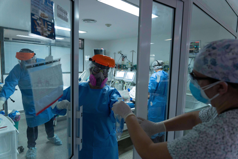 Carina Balasini recibe un instrumento para intubar a una paciente. Algunas enfermeras no entran a la sala para poder acercar las herramientas a los médicos.