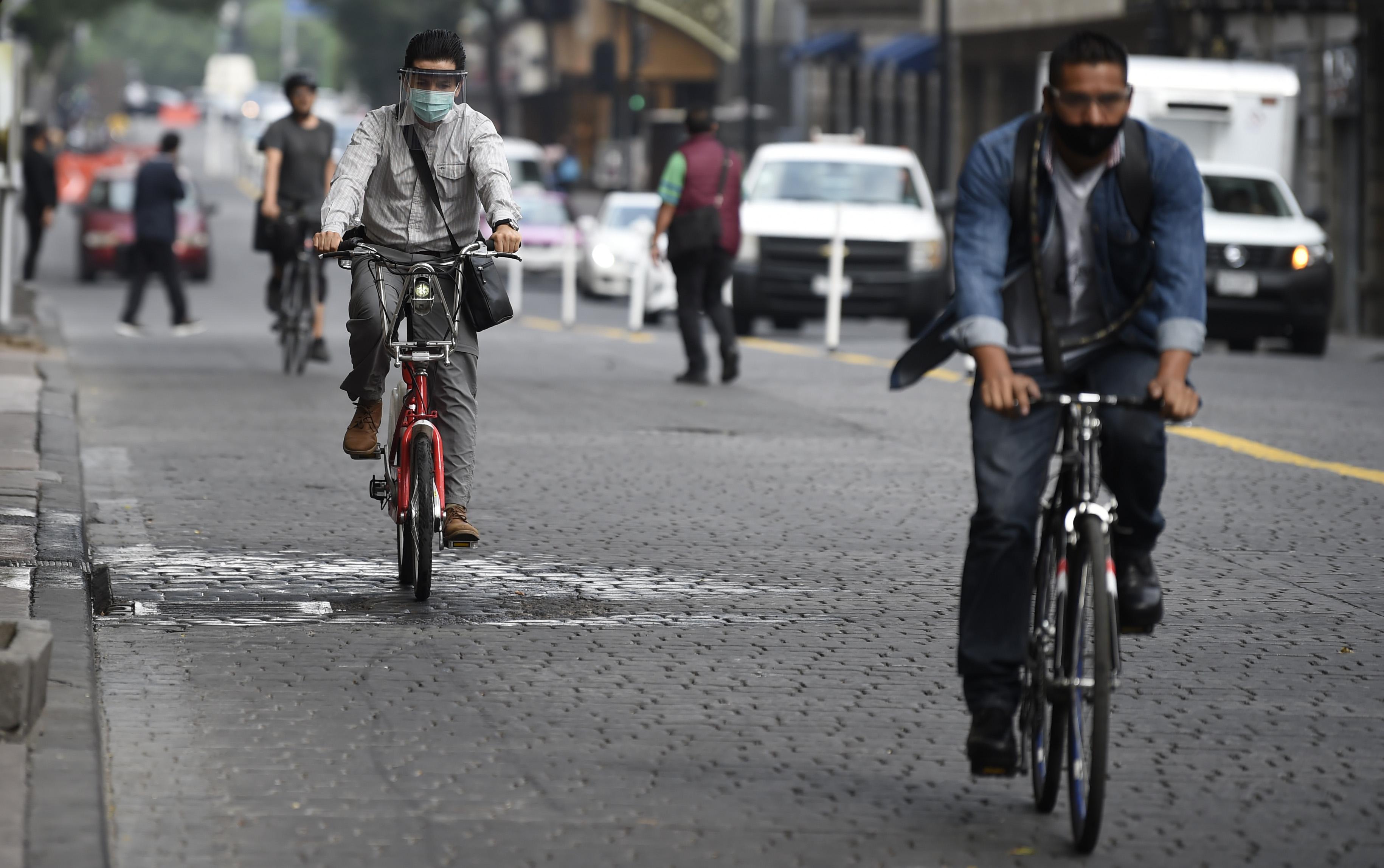 La gente viaja en una calle en el centro histórico de la Ciudad de México habilitada para ciclistas y peatones, como parte de las medidas de reapertura adoptadas por el gobierno el 29 de junio de 2020 durante la pandemia COVID-19. (Foto: ALFREDO ESTRELLA / AFP)