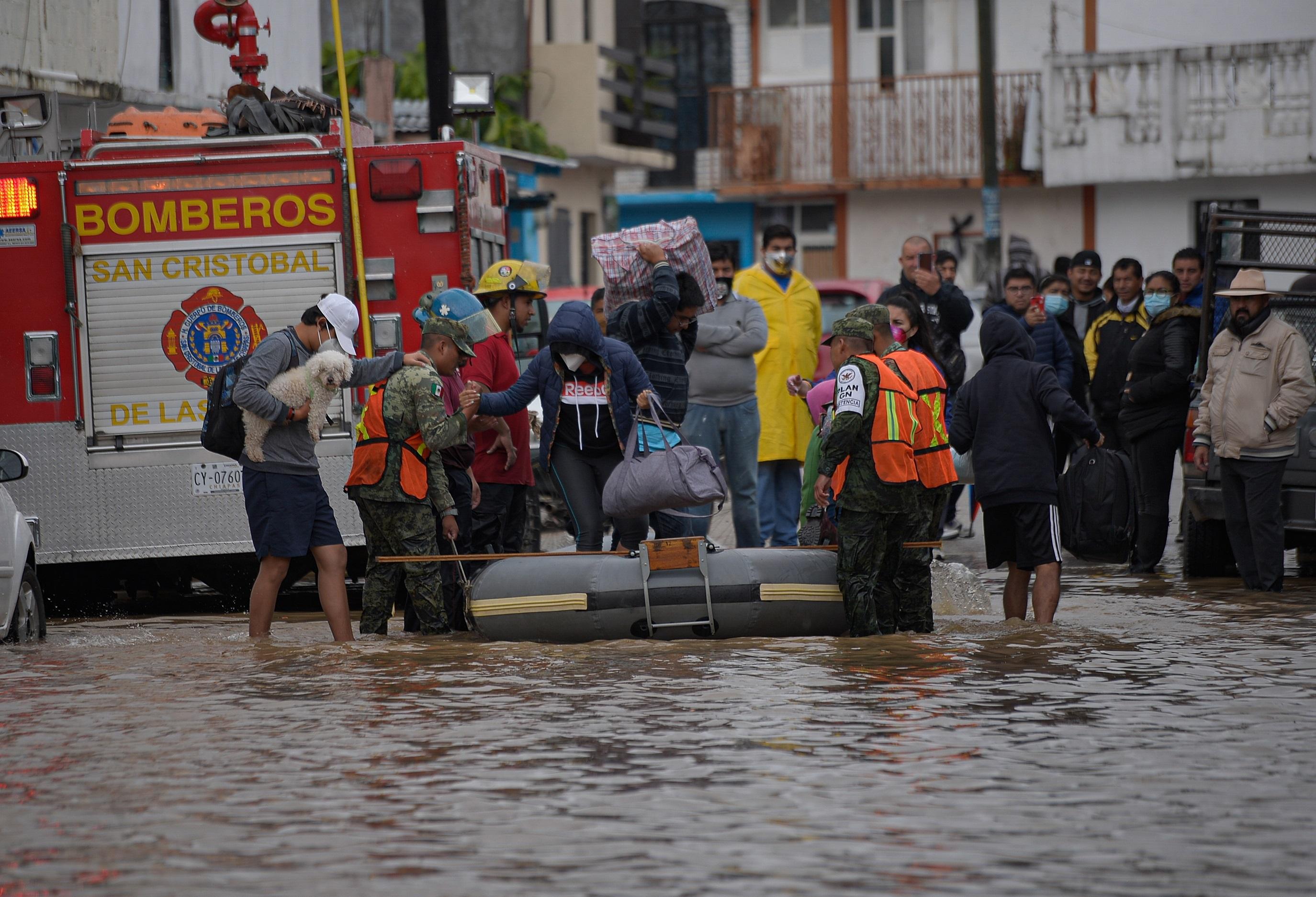 Policías estatales evacuan a familias de la zona inundada este viernes, en el municipio de San Cristóbal de las Casas, en el estado de Chiapas.