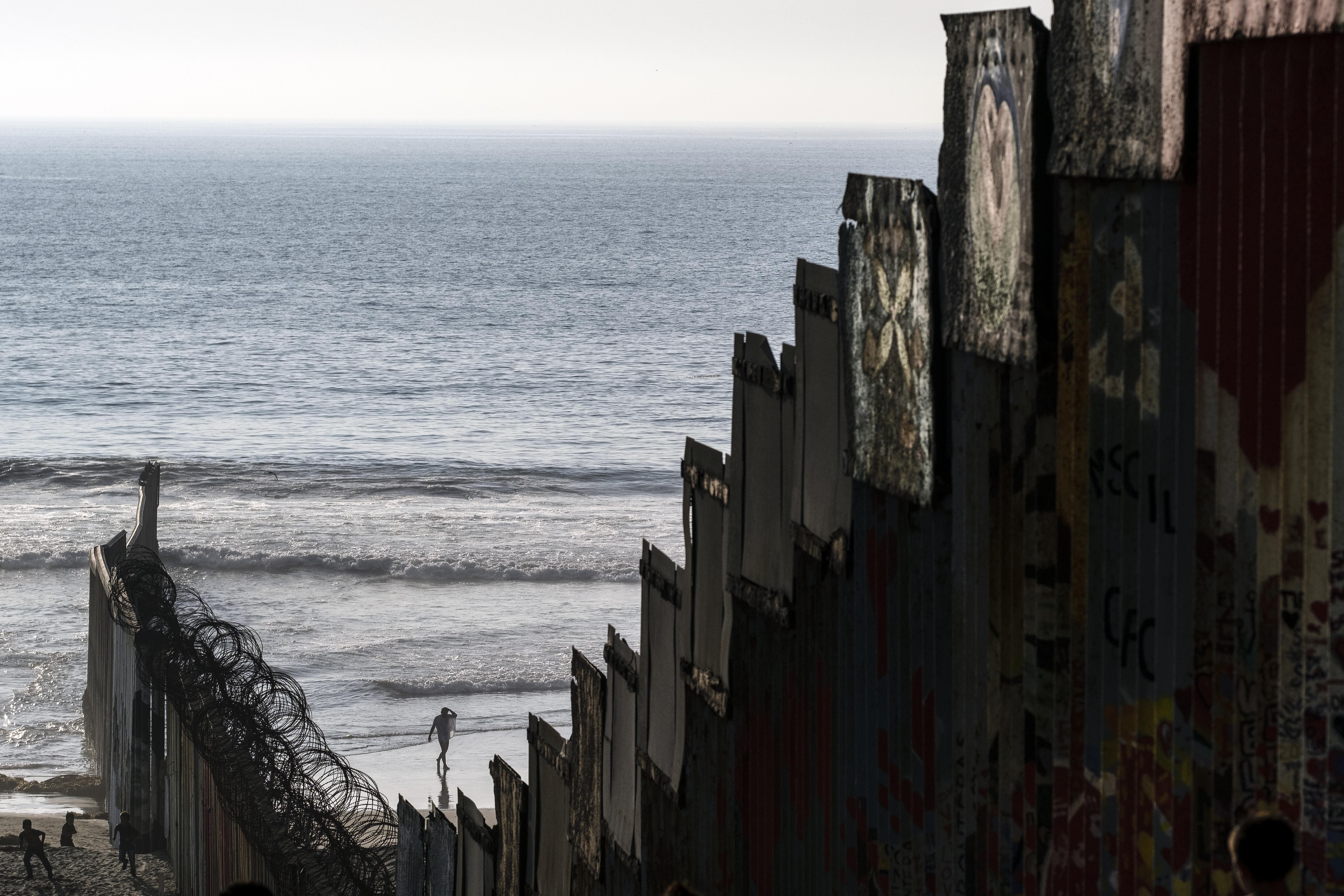 Un migrante camina en la playa (D) después de nadar a través de la valla fronteriza entre Estados Unidos y México antes de rendirse a la patrulla fronteriza, visto desde Playas de Tijuana, estado de Baja California, México, el 3 de octubre de 2020, en medio del COVID-19. pandemia de coronavirus.