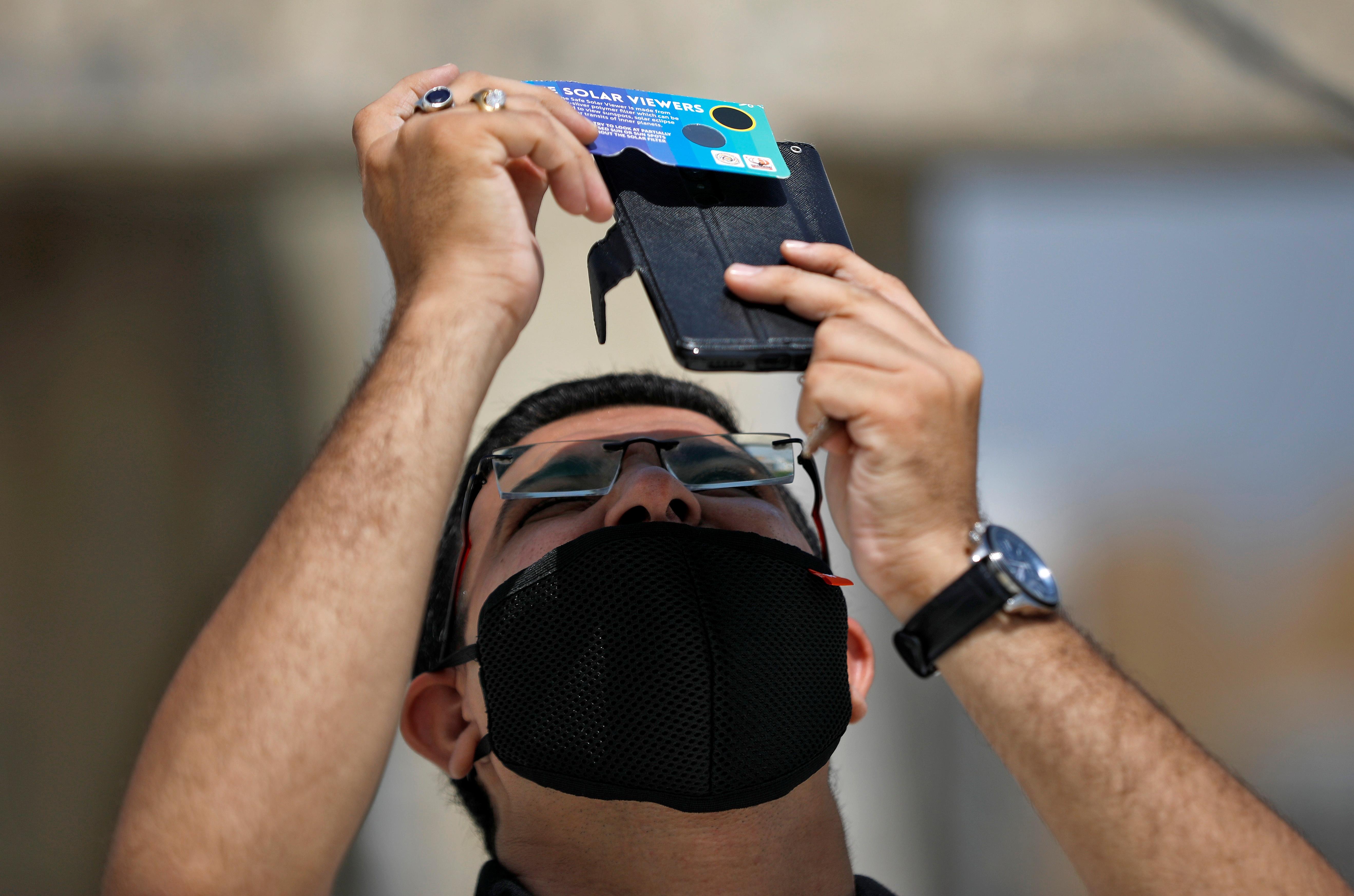 Un hombre ve el eclipse desde su celular