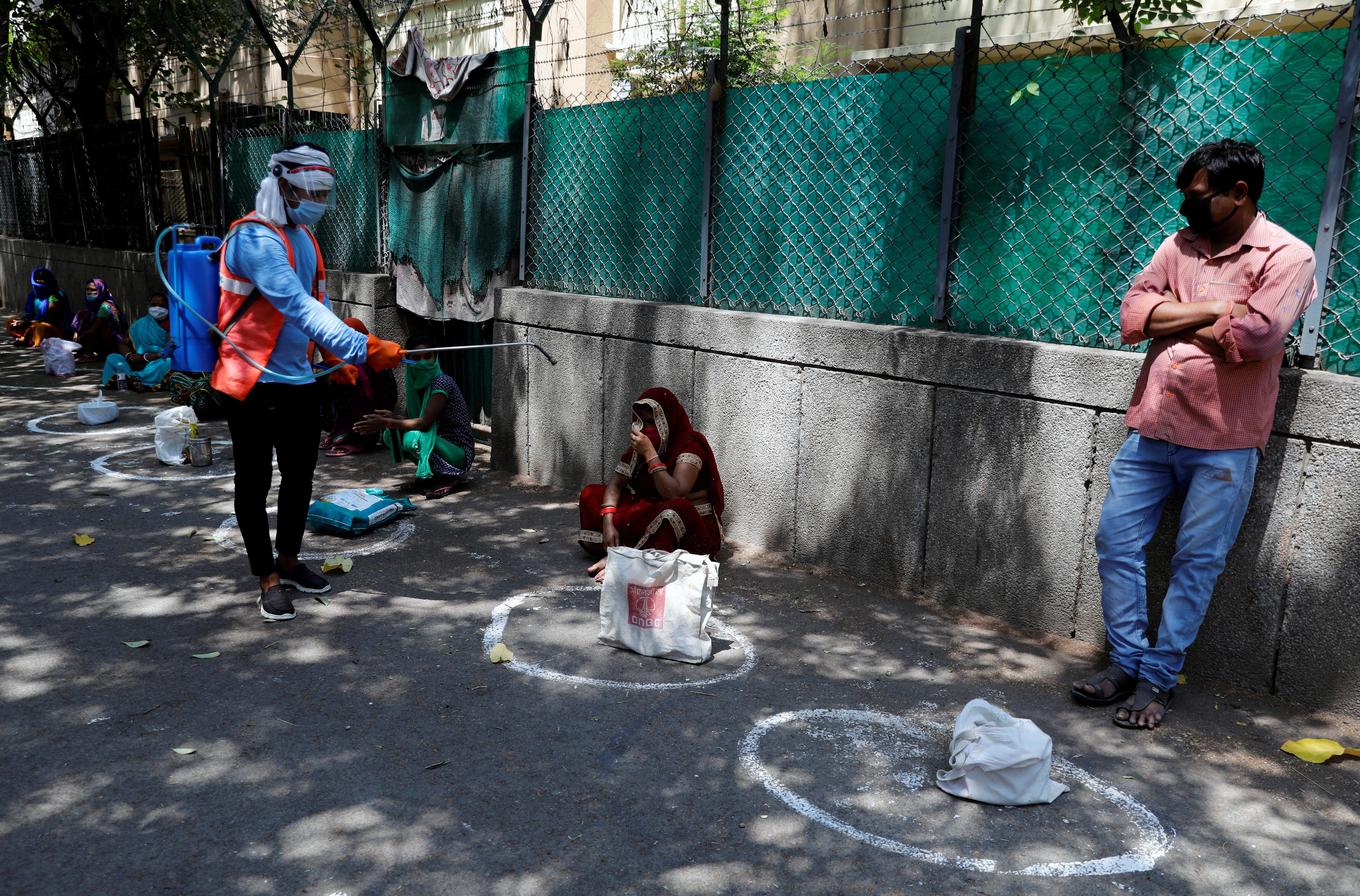 Un trabajador municipal rocía desinfectante en las bolsas de la gente, mientras mantienen el distanciamiento social en una fila para recibir alimentos gratuitos distribuidos por el gobierno en Nueva Delhi, India, el 21 de abril de 2020. REUTERS/Anushree Fadnavis