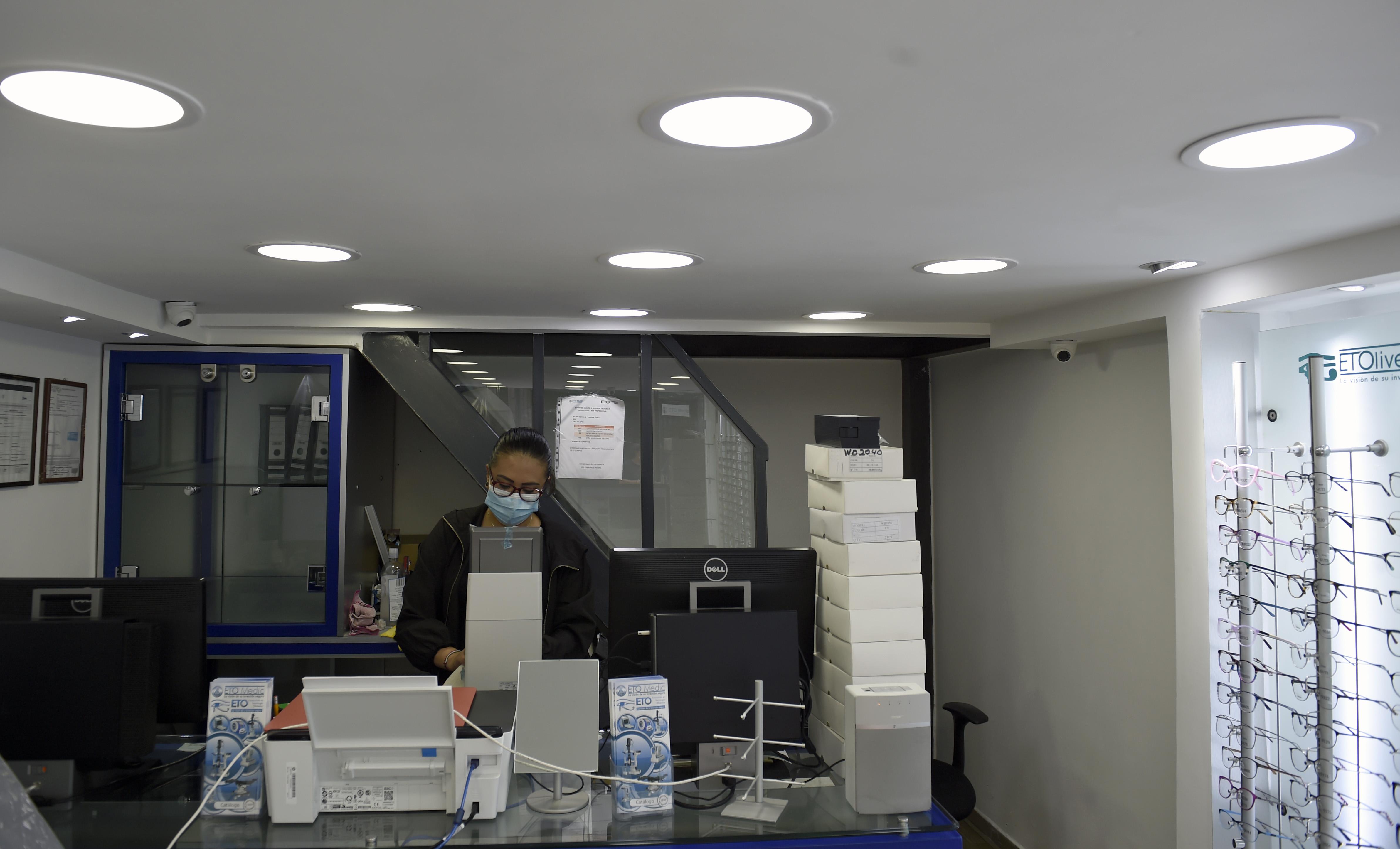 El empleado de una óptica limpia antes de volver a abrir en la Ciudad de México el 29 de junio de 2020 durante la pandemia de COVID-19. (Foto: ALFREDO ESTRELLA / AFP)
