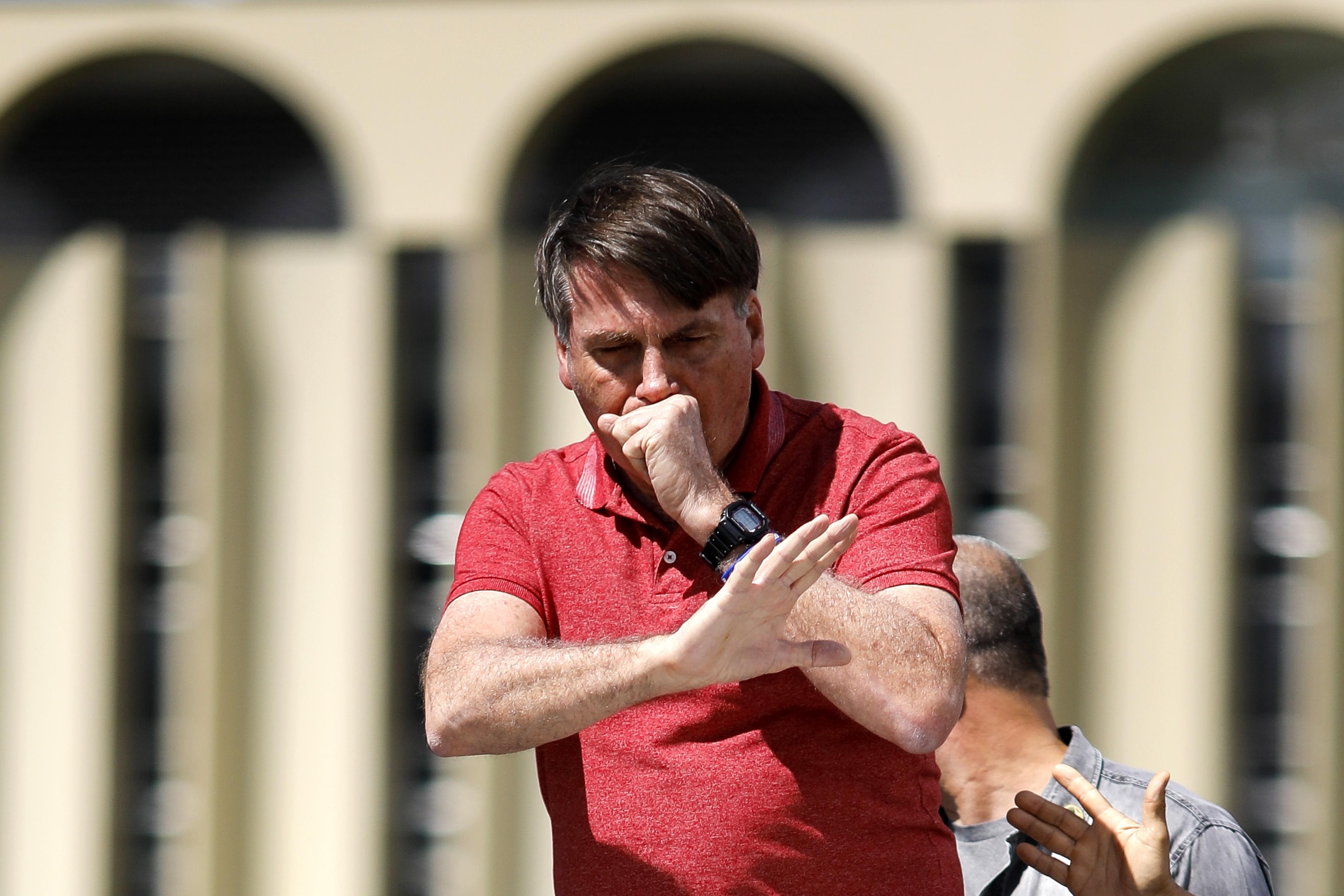 Bolsonaro tosiendo durante un discurso ante sus seguidores que protestaron contra los confinamientos impuestos en algunos estados, el 19 de abril pasado. A contramano de los recomendado por la OMS de toser sobre los codos, el presidente tose en su mano (Photo by Sergio LIMA / AFP)