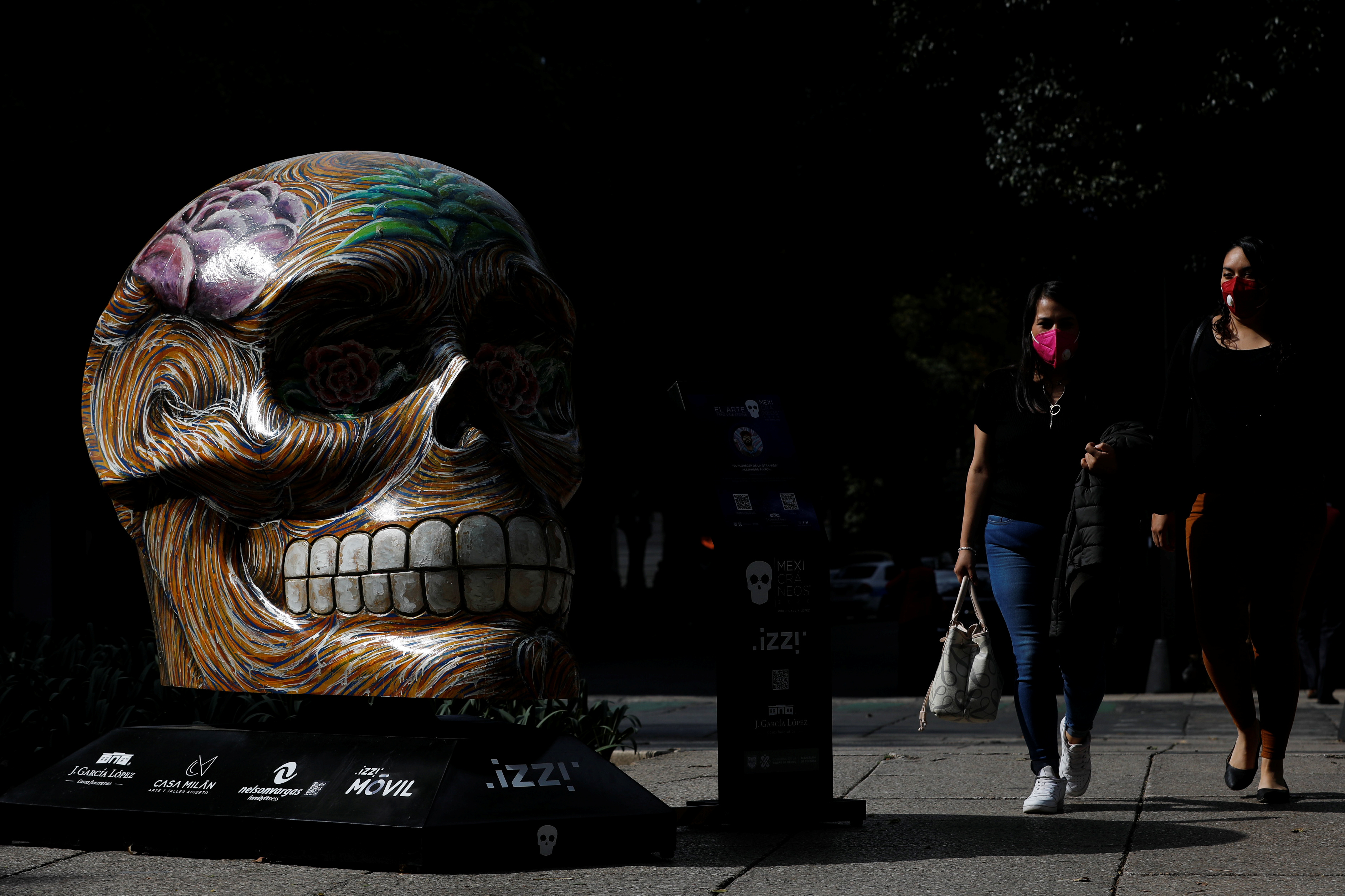 People walk by a colorful skull exhibited at Reforma avenue, as part of the festivities in the lead-up to the Day of the Dead celebration, in Mexico City, Mexico October 13, 2020. REUTERS/Carlos Jasso