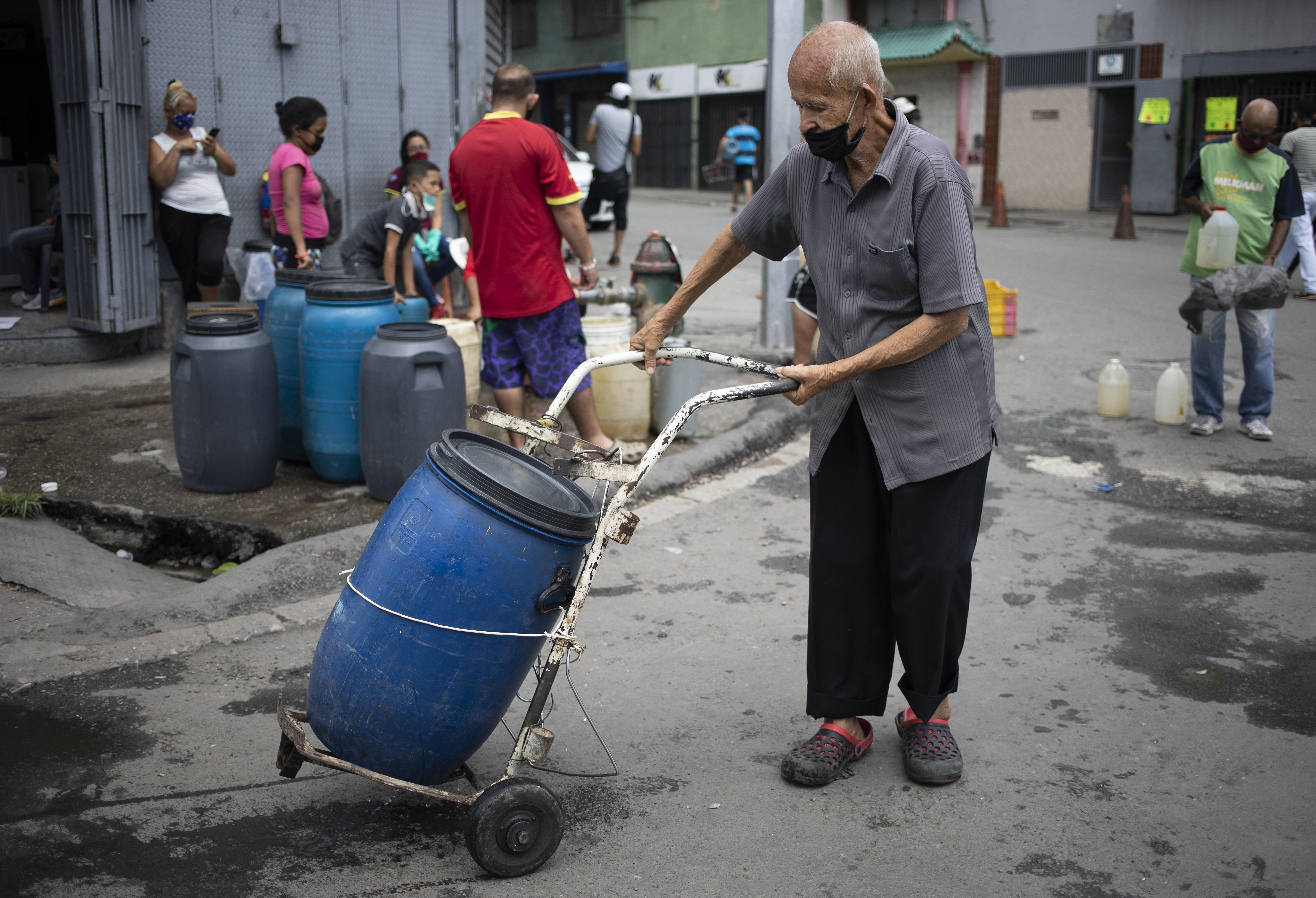 Un hombre, con mascarilla para protegerse del coronavirus, empuja un carrito con un recipiente que llenó de agua en un grifo callejero, en Caracas, Venezuela, el 20 de junio de 2020. El suministro de agua en Venezuela es tan precario que en vecindarios pobres empiezan a gestionar canalizaciones privadas o a excavar pozos poco profundos. (AP Foto/Ariana Cubillos)