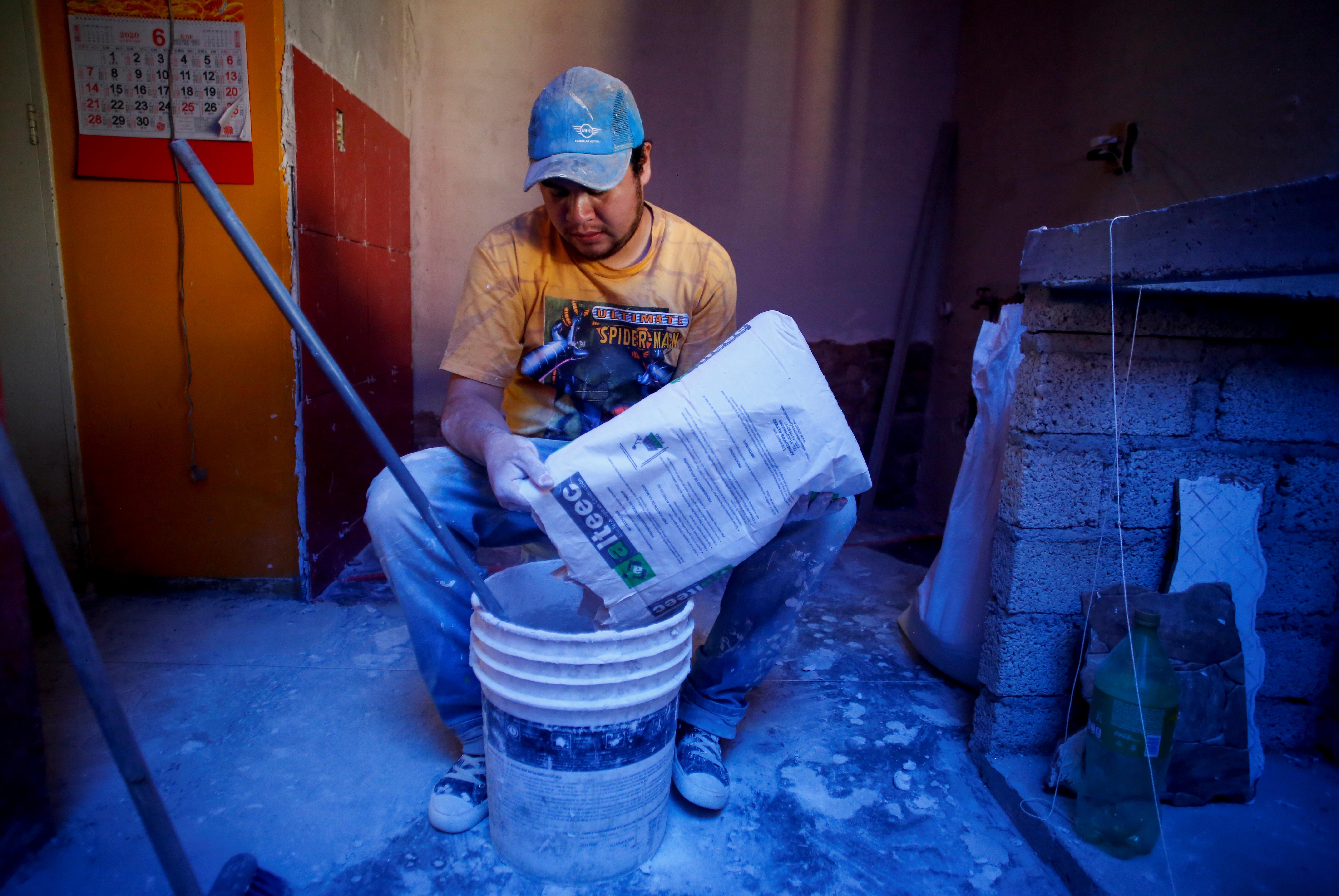 Miguel Flores Torres vierte cemento mientras remodela una casa en Villa Olímpica, Ciudad de México, México, 17 de junio de 2020. Foto: REUTERS / Gustavo Graf.