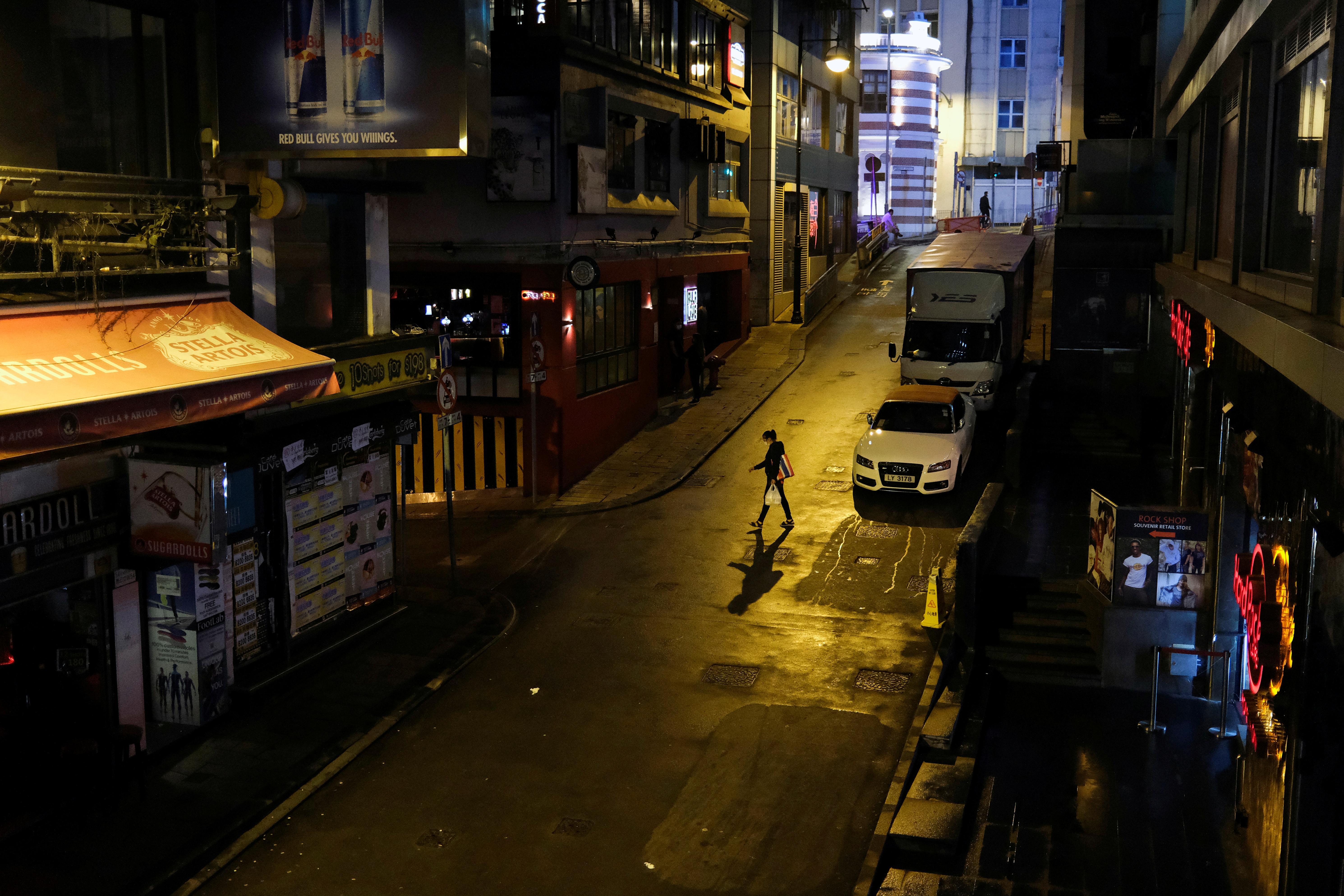 Una mujer cruza la calle en una zona de bares totalmente desierta y con todos los comercios cerrados en Hong Kong (REUTERS/Tyrone Siu)
