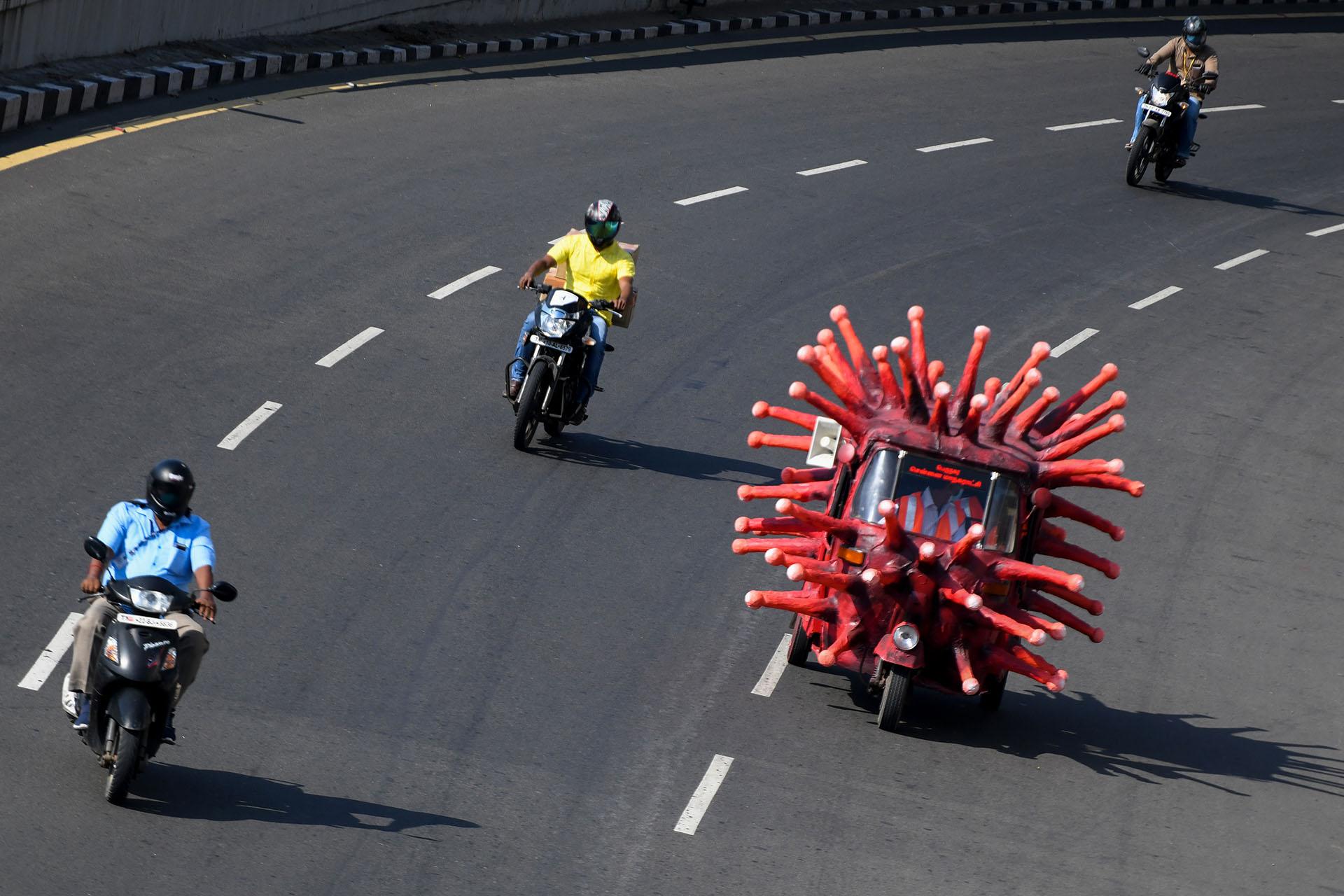 Un trabajador municipal de la salud conduce un auto-rickshaw decorado como una imagen de coronavirus a lo largo de una carretera para concienciar sobre el coronavirus COVID-19 en Chennai el 23 de abril de 2020. (Foto de Arun SANKAR / AFP)