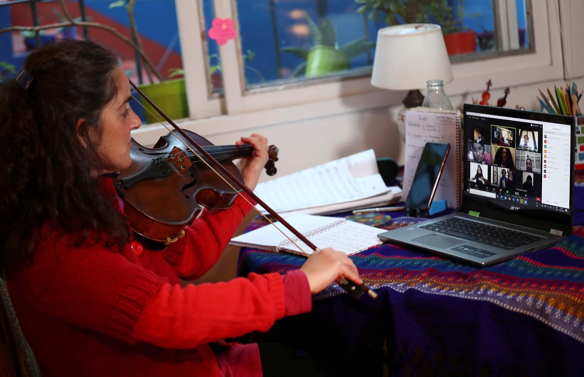 Clarisa Orfila, profesora de violín, le ensaña a sus alumnos por zoom en una foto que data del 16 de julio, cuando todavía faltaban meses para llegar al pico de contagios en el país
