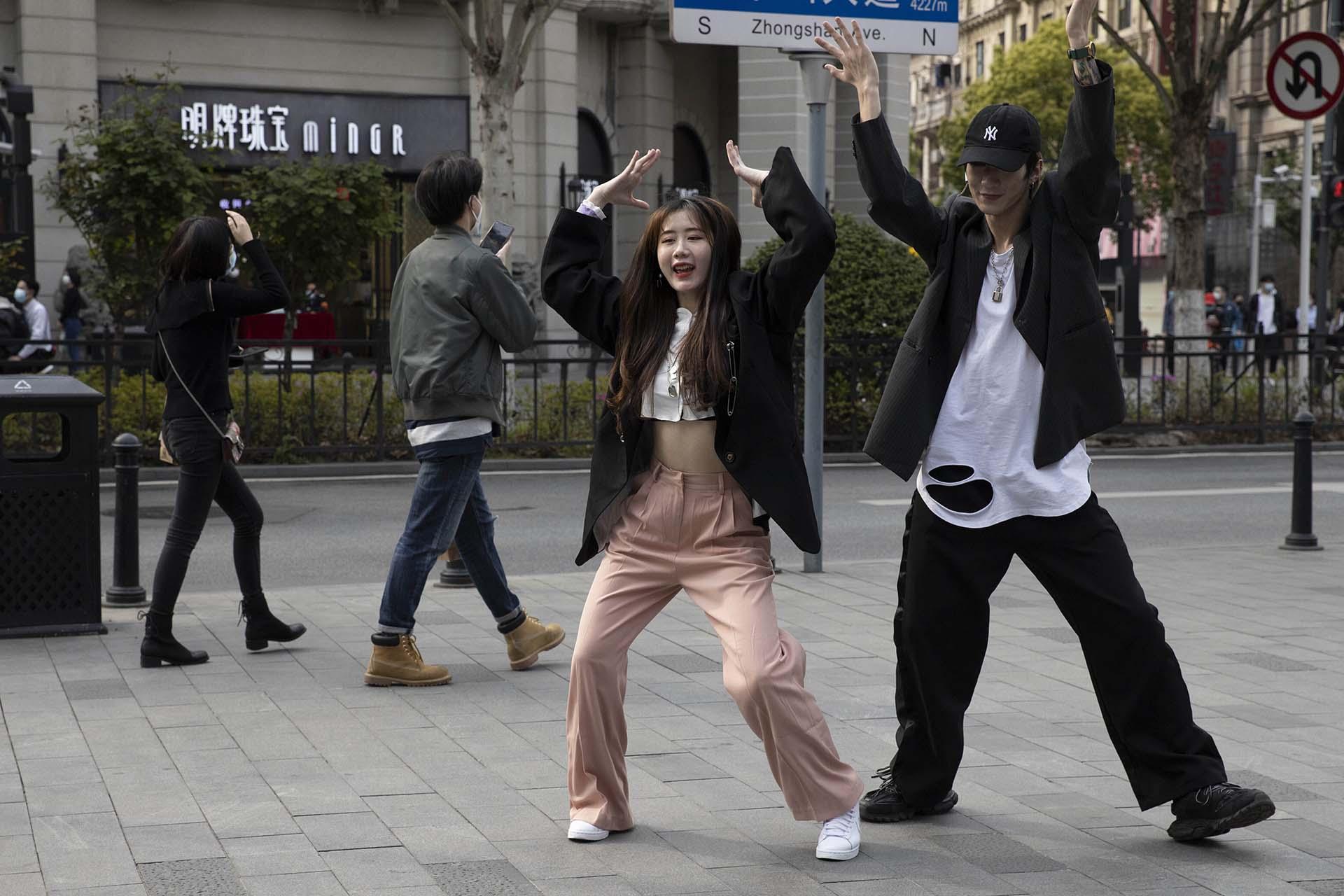 Una pareja de jóvenes se quitan sus máscaras faciales para grabar una coreografía en las calles de Wuhan, China (AP Photo/Ng Han Guan)