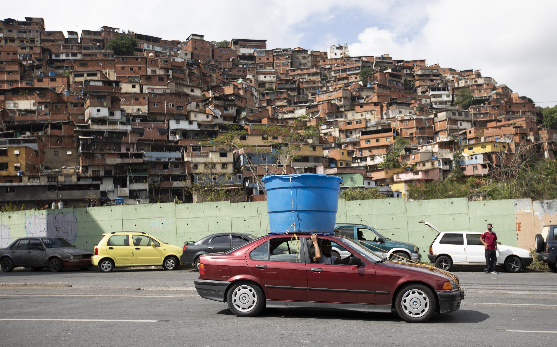 Un auto circula con un enorme recipiente de plástico con agua sobre el techo, en el vecindario humilde de Petare, en Caracas, Venezuela, el 5 de junio de 2020. Se estima que el 86% de los venezolanos reportó problemas con el suministro de agua, incluyendo un 11% que no tiene, según una encuesta realizada por la ONG Observatorio Venezolano de Servicios Públicos entre 4.500 residentes en abril. (AP Foto/Ariana Cubillos)
