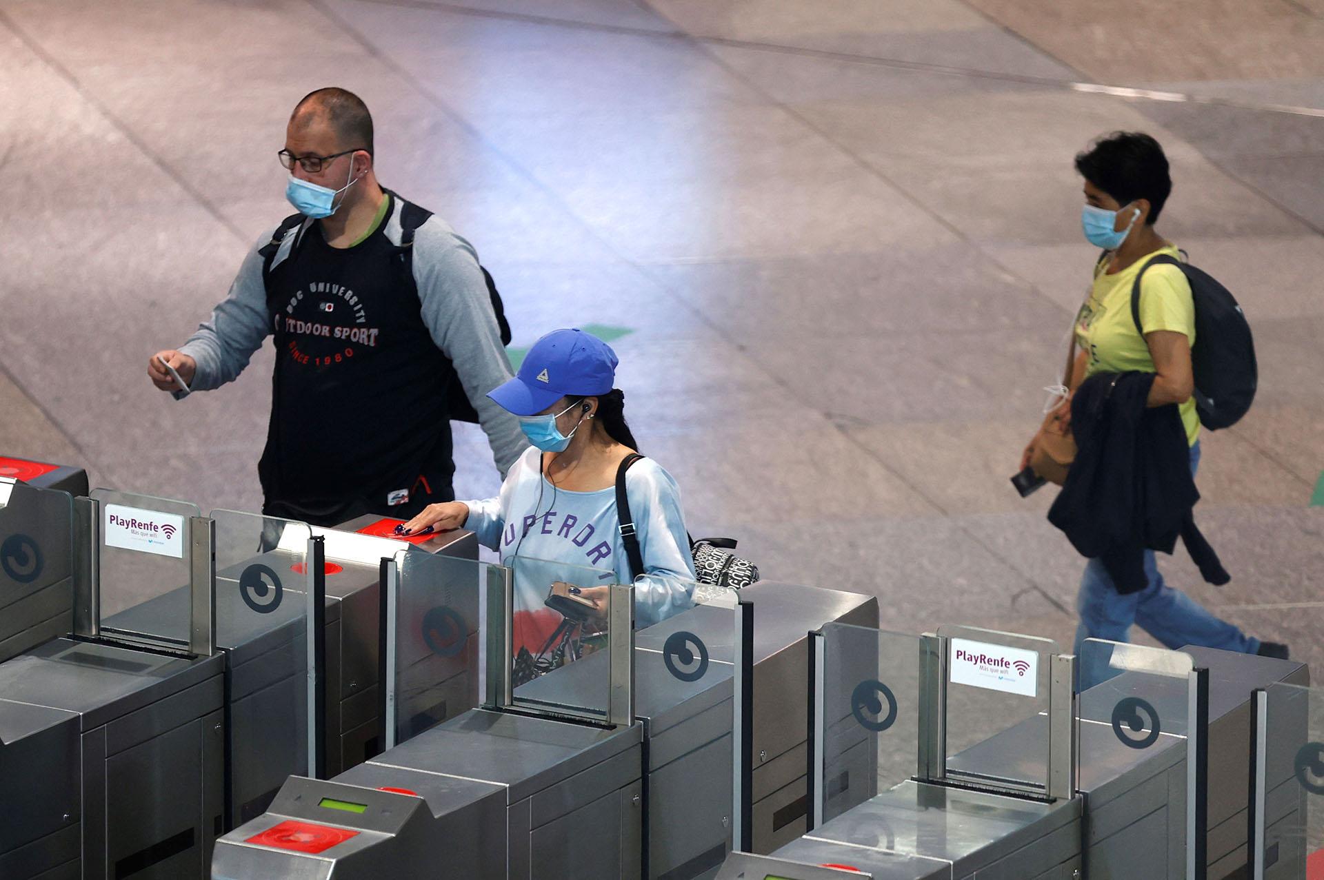 Varias personas acceden al Cercanías en la estación de Atocha en Madrid este lunes durante el primer día de la fase 0 de la desescalada que vive la comunidad. La oferta de todo el transporte público aumentará un 90% en hora punta en la Comunidad de Madrid para evitar aglomeraciones. (EFE/Chema Moya)