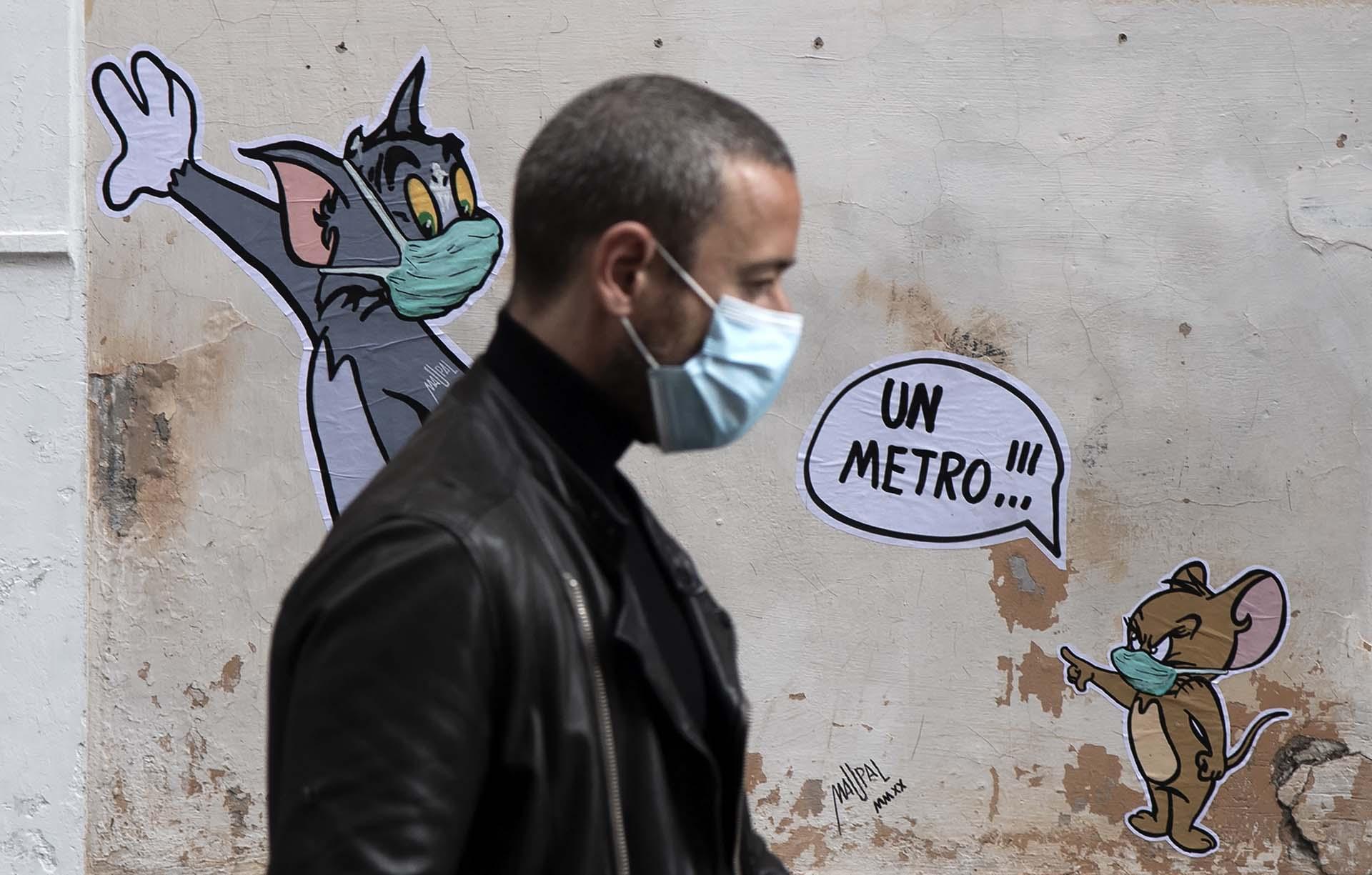 Un hombre pasa frente a un mural del artista Maupal que homenajea a los legendarios Tom y Jerry en una calle de Roma.