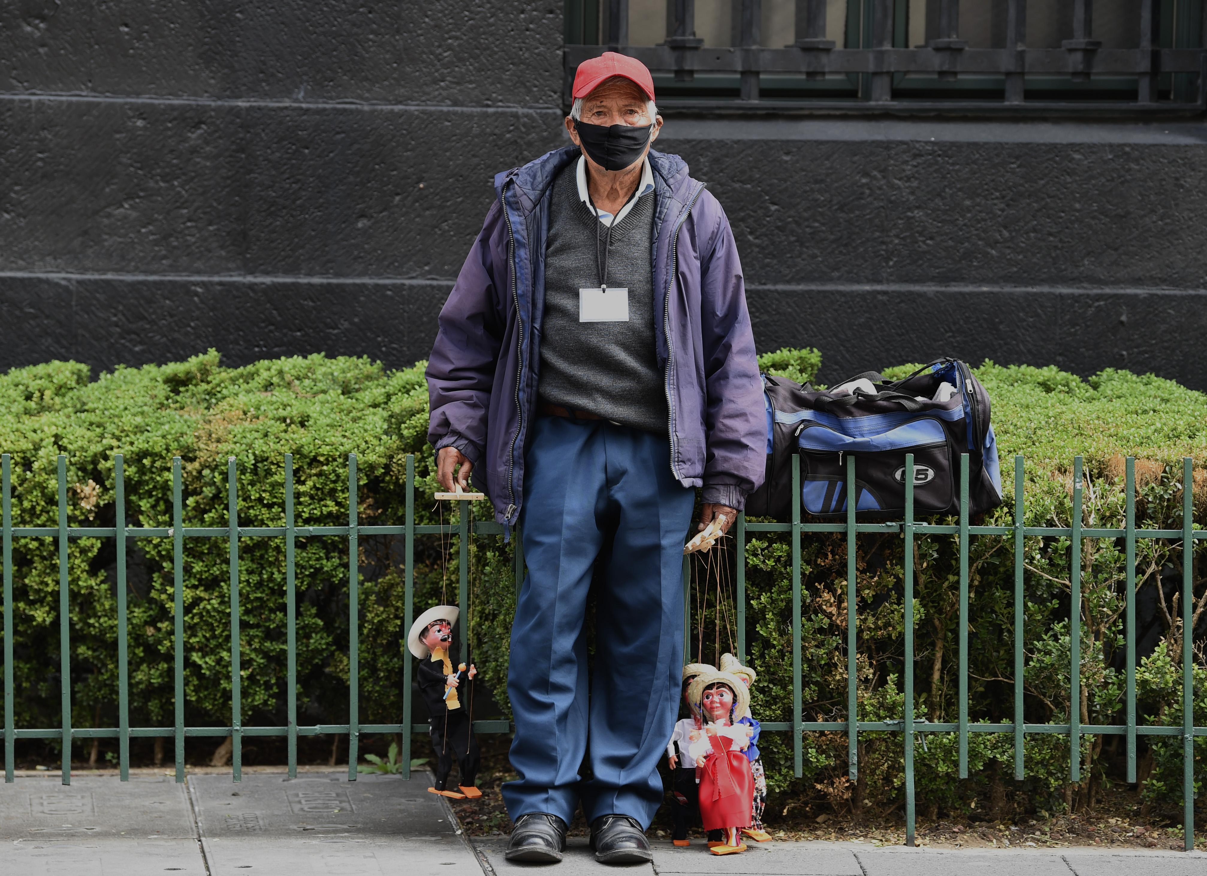 Un vendedor ambulante vende títeres hechos a mano en la Ciudad de México, el 29 de junio de 2020 durante la pandemia COVID-19. (Foto: ALFREDO ESTRELLA / AFP)