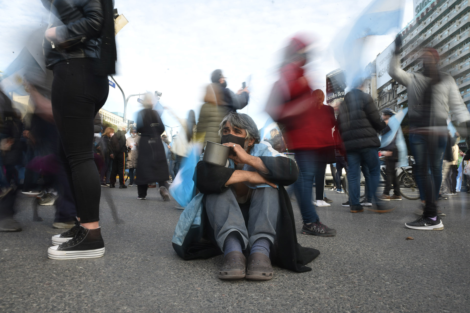 Un hombre pide limosna en el medio de la protesta