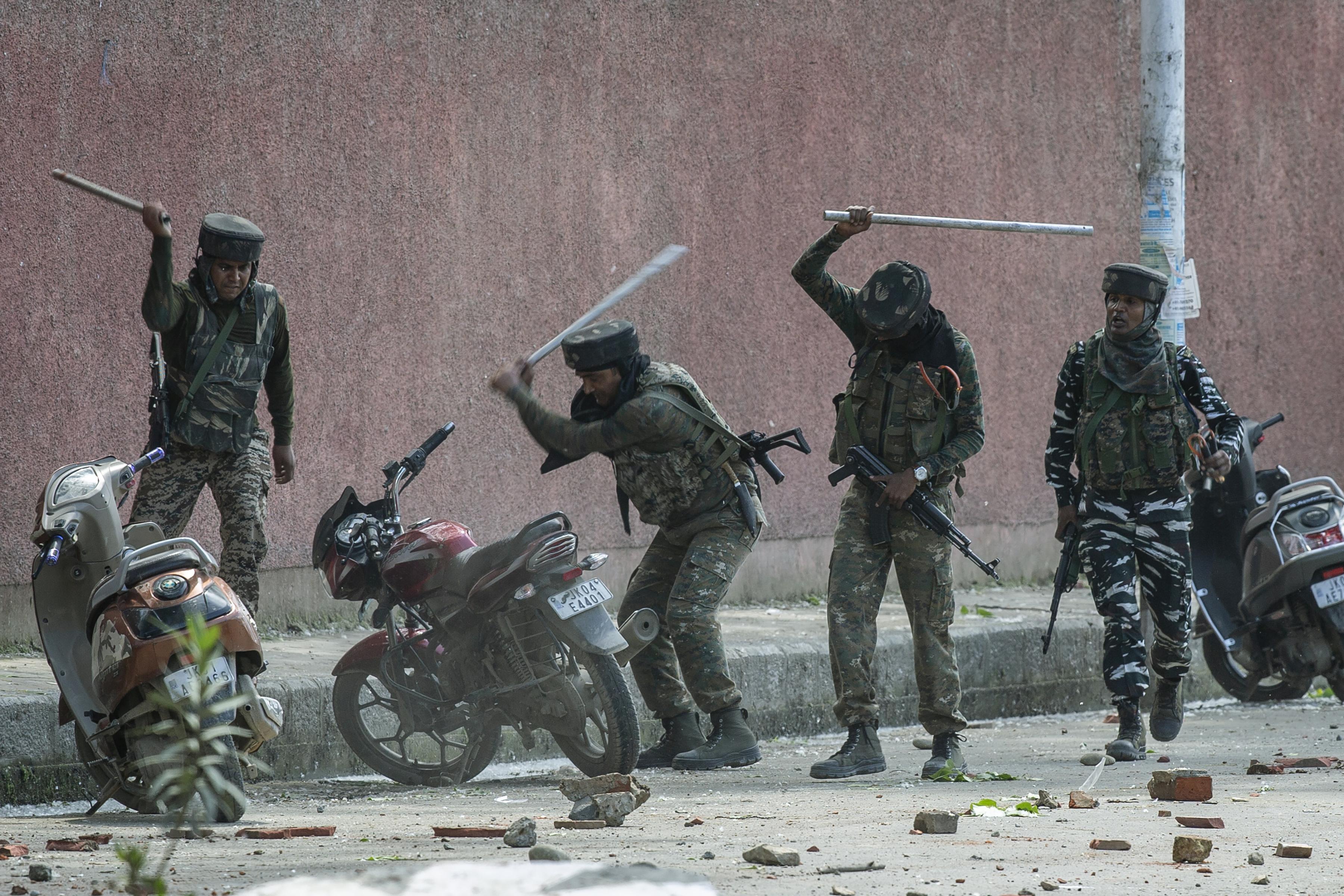 Soldados paramilitares indios rompen motocicletas estacionadas afuera de una universidad mientras chocan con estudiantes que protestaban por la presunta violación de una niña de 3 años en Srinagar, Cachemira controlada por la India, 14 de mayo de 2019. (Foto AP / Dar Yasin)