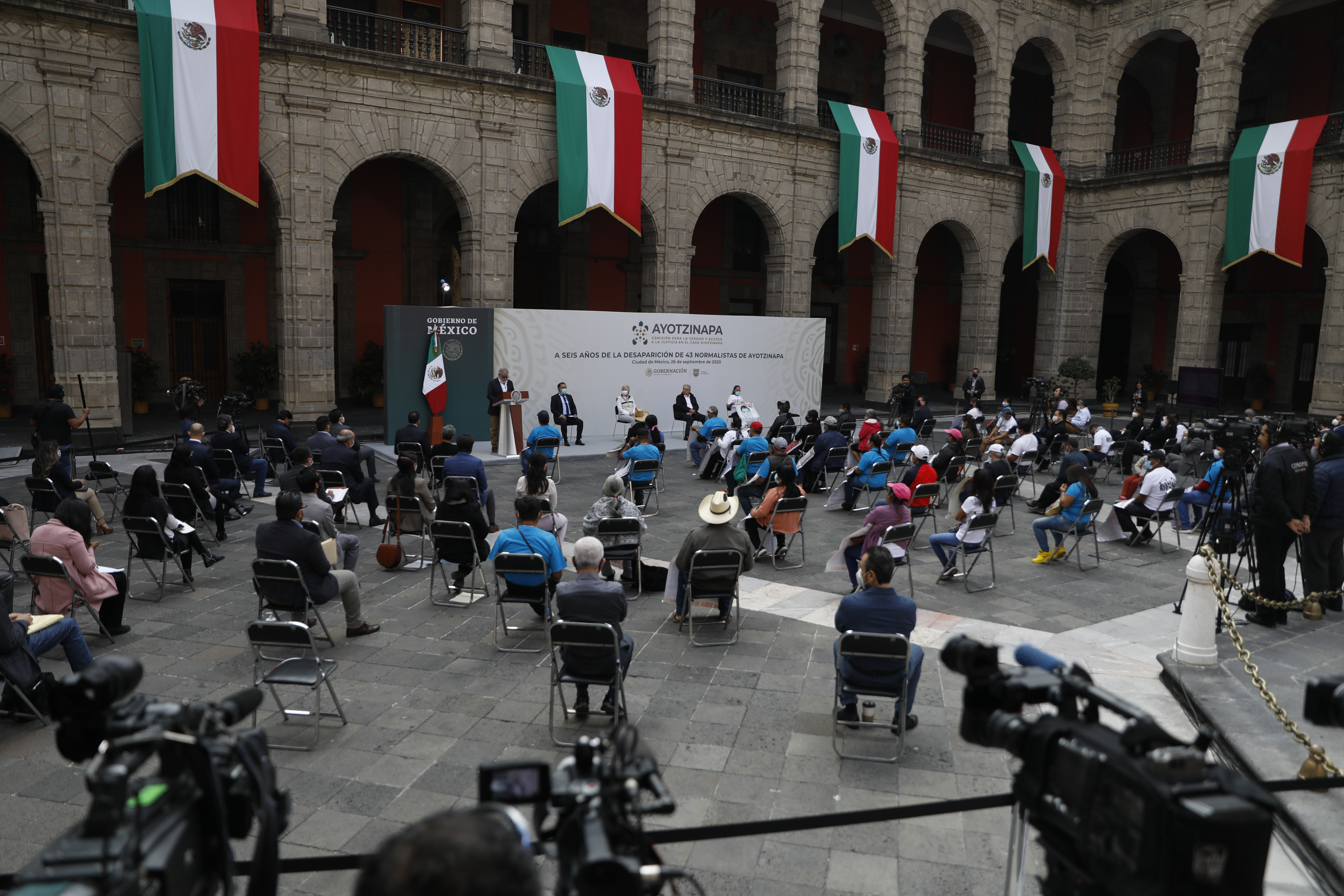 Mexico's President Andres Manuel Lopez Obrador, left, and Deputy Interior Secretary Alejandro Encinas, right, applaud for Maria Martinez, mother of Miguel Angel Hernandez Martinez, as she is introduced as a representative of the family members of 43 missing students from the Rural Normal School of Ayotzinapa, during an event to update the ongoing investigations on the sixth anniversary of the students' disappearance, at the National Palace in Mexico City, Saturday, Sept. 26, 2020. (AP Photo/Rebecca Blackwell)