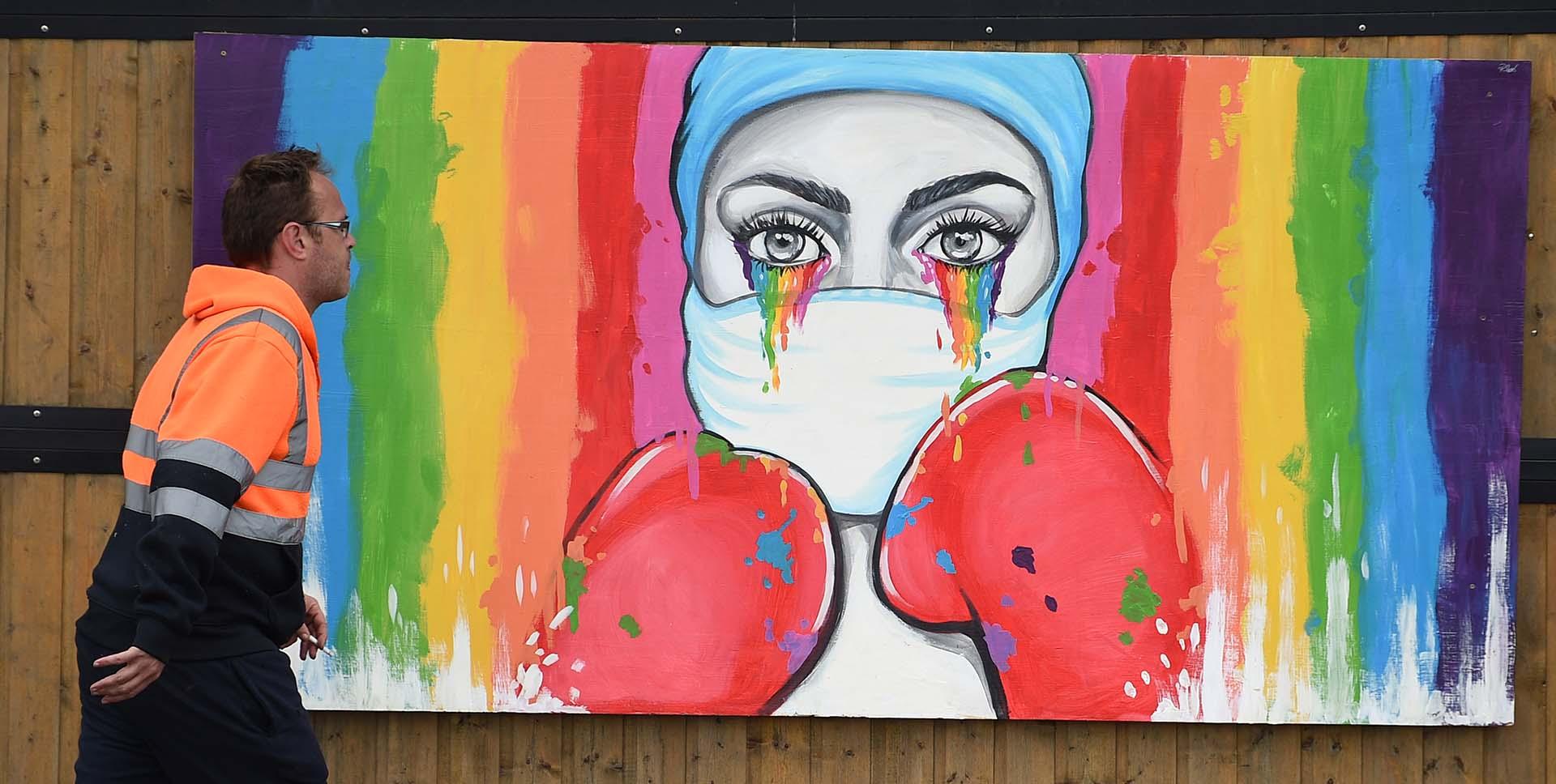 Un hombre pasa frente a un mural de la artista Rachel List en tributo a los trabajadores del servicio público de salud del NHS en Pontefract, al norte de Inglaterra.