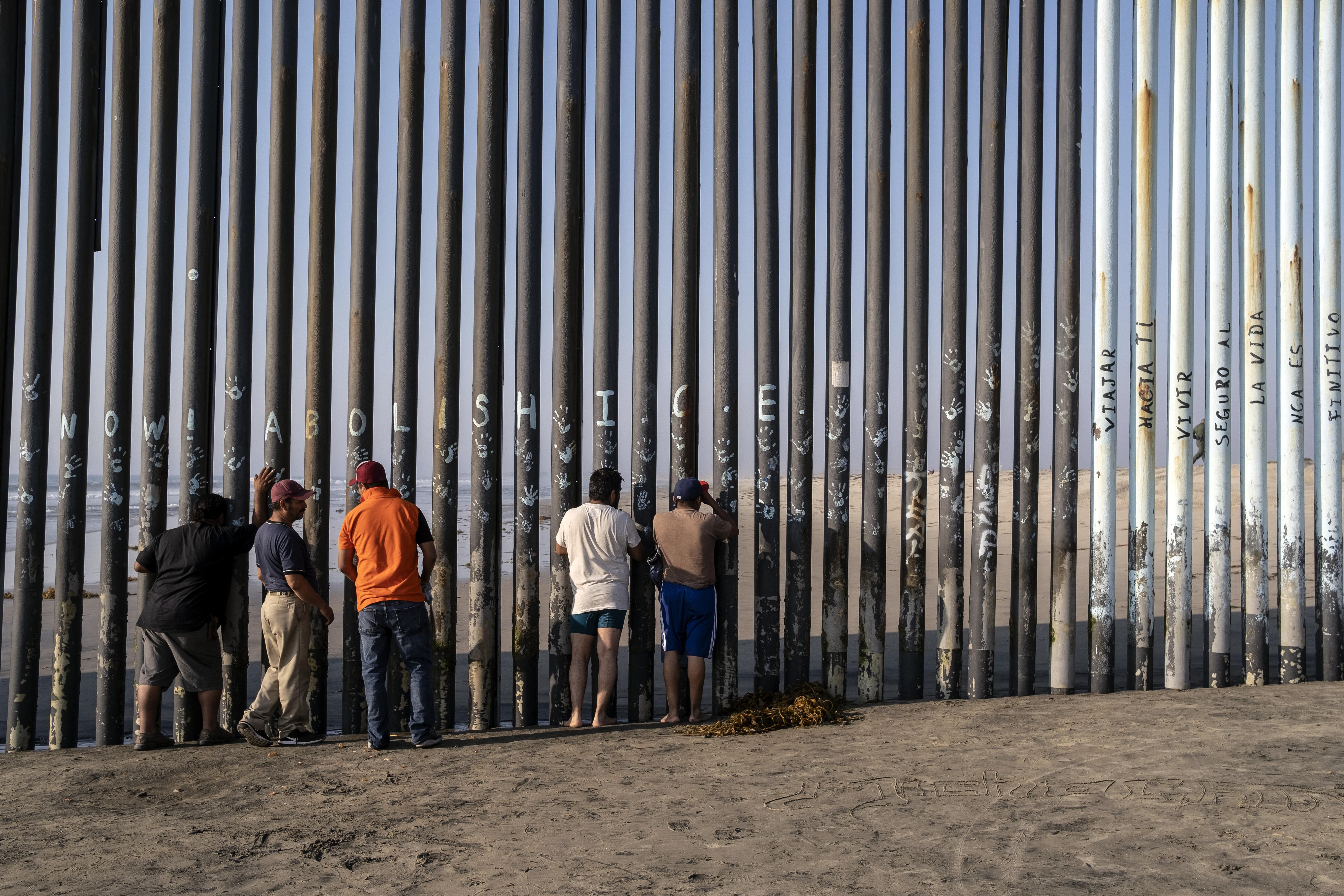 Hombres miran a través de la valla fronteriza entre Estados Unidos y México en Playas de Tijuana, estado de Baja California, México, el 3 de octubre de 2020, en medio de la pandemia del COVID-19.