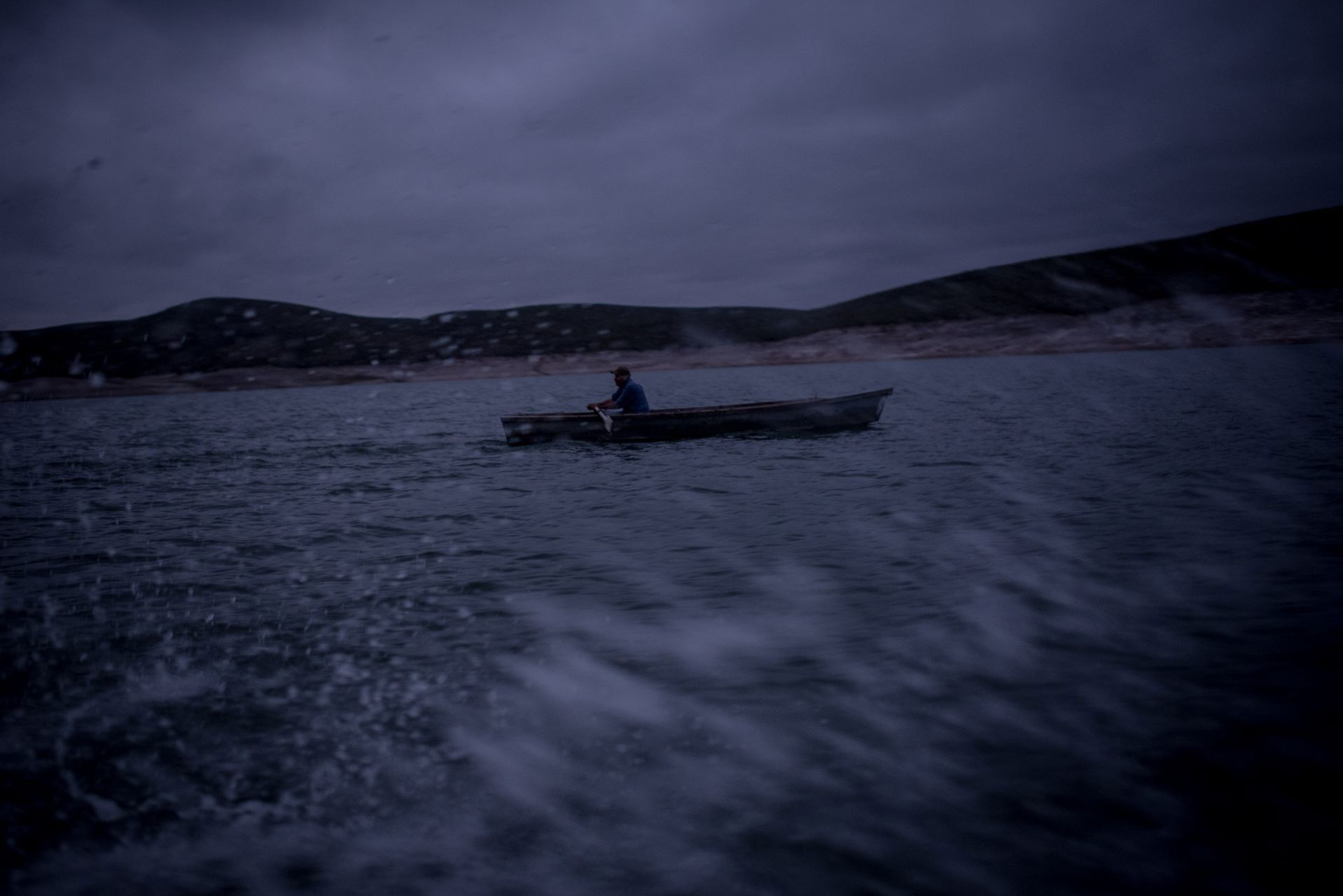 Un pescador avanza al despuntar el día en la presa