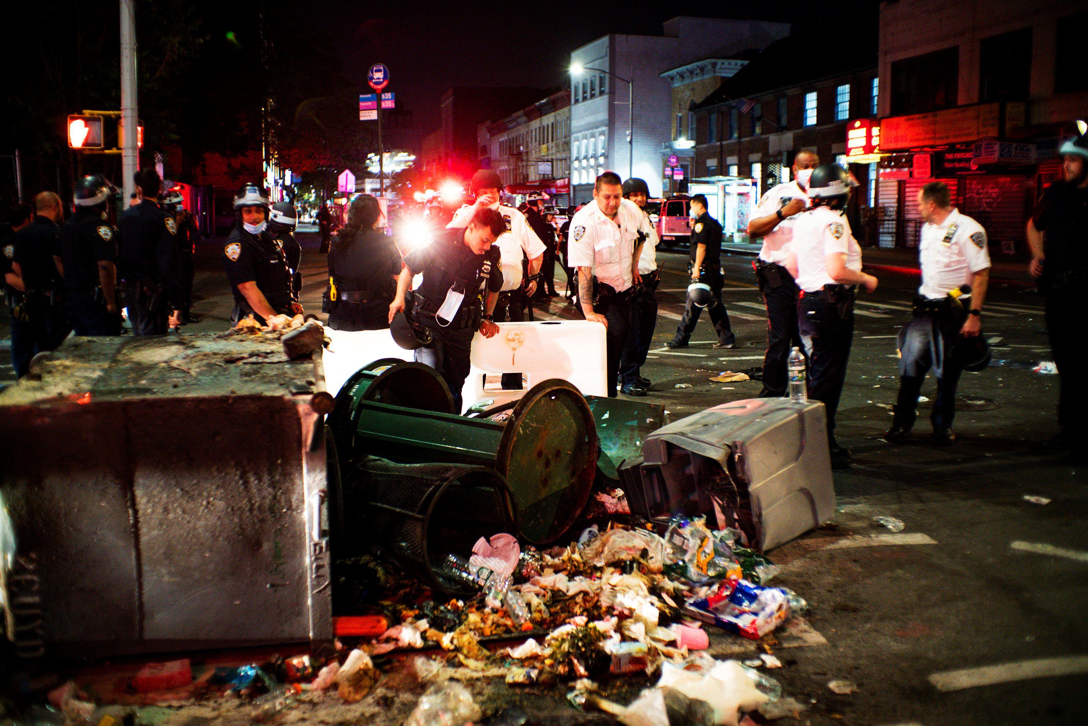 Oficiales revisan los destrozos y la basura arrojada por la protesta
